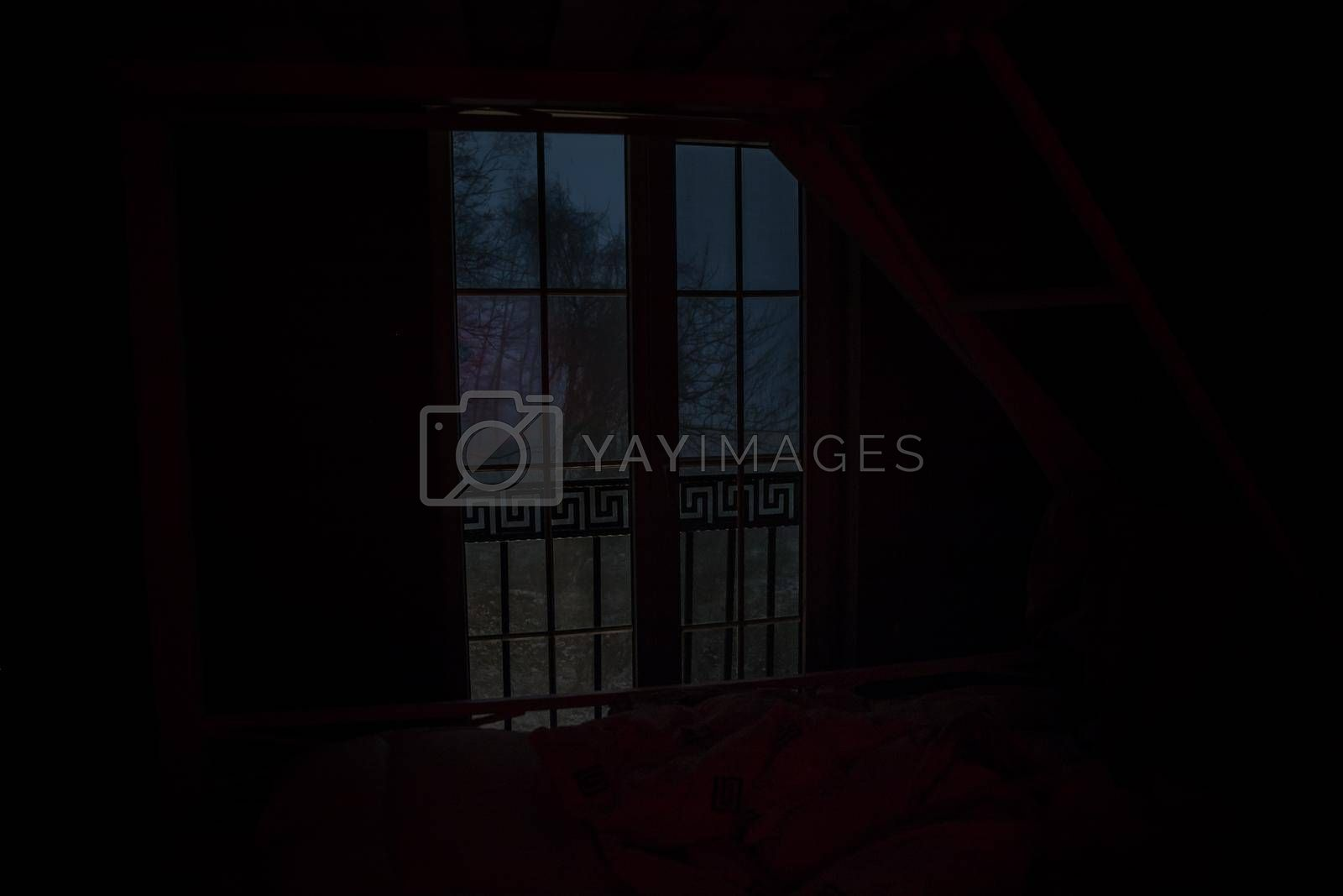 View from window frame to the winter forest at night. Selective focus. Long exposure shot