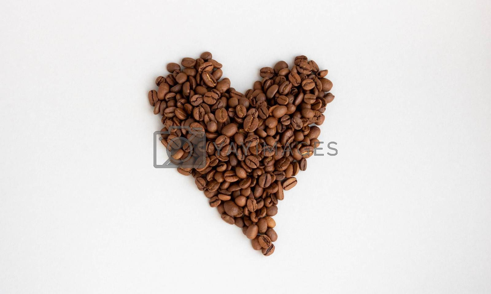Heart-shaped coffee beans isolated on a gray background.