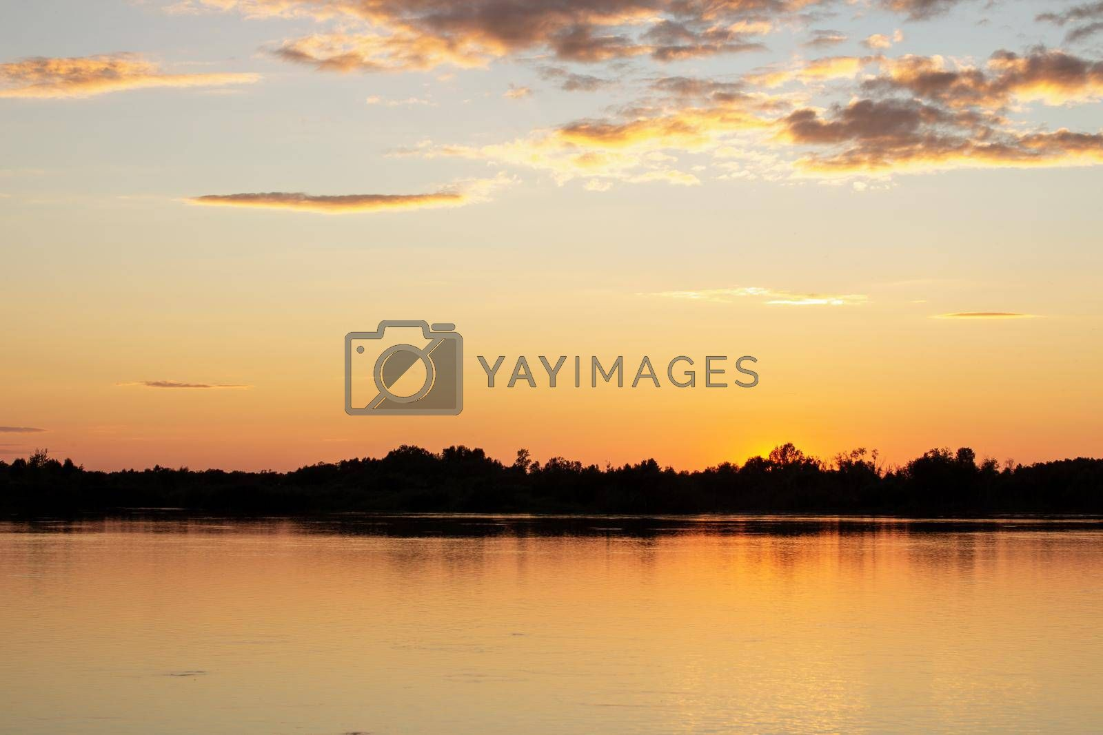 A colorful sunny sunset is reflected on the surface of the calm lake. by AnatoliiFoto