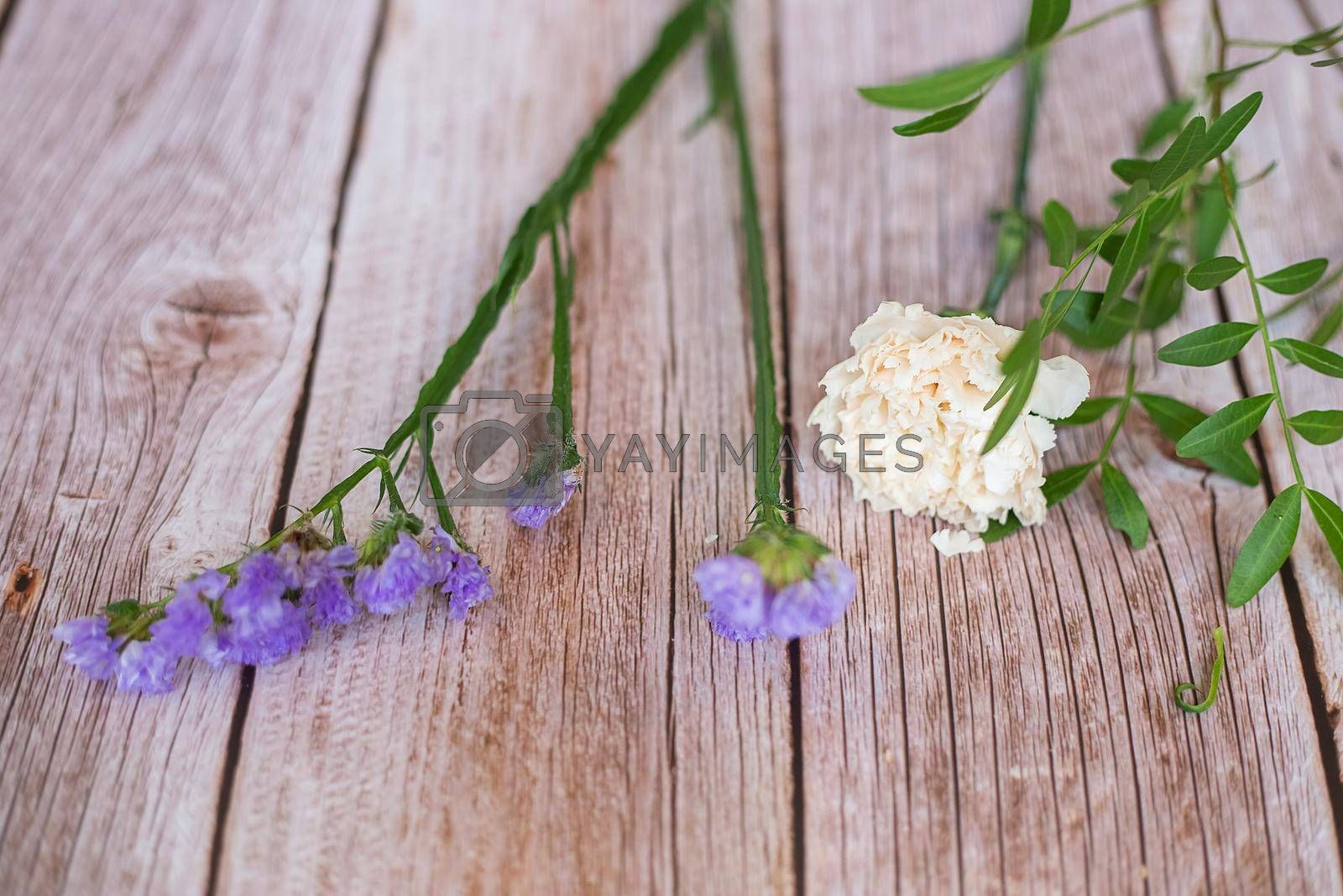 The florist desktop on light wooden background with place for text.