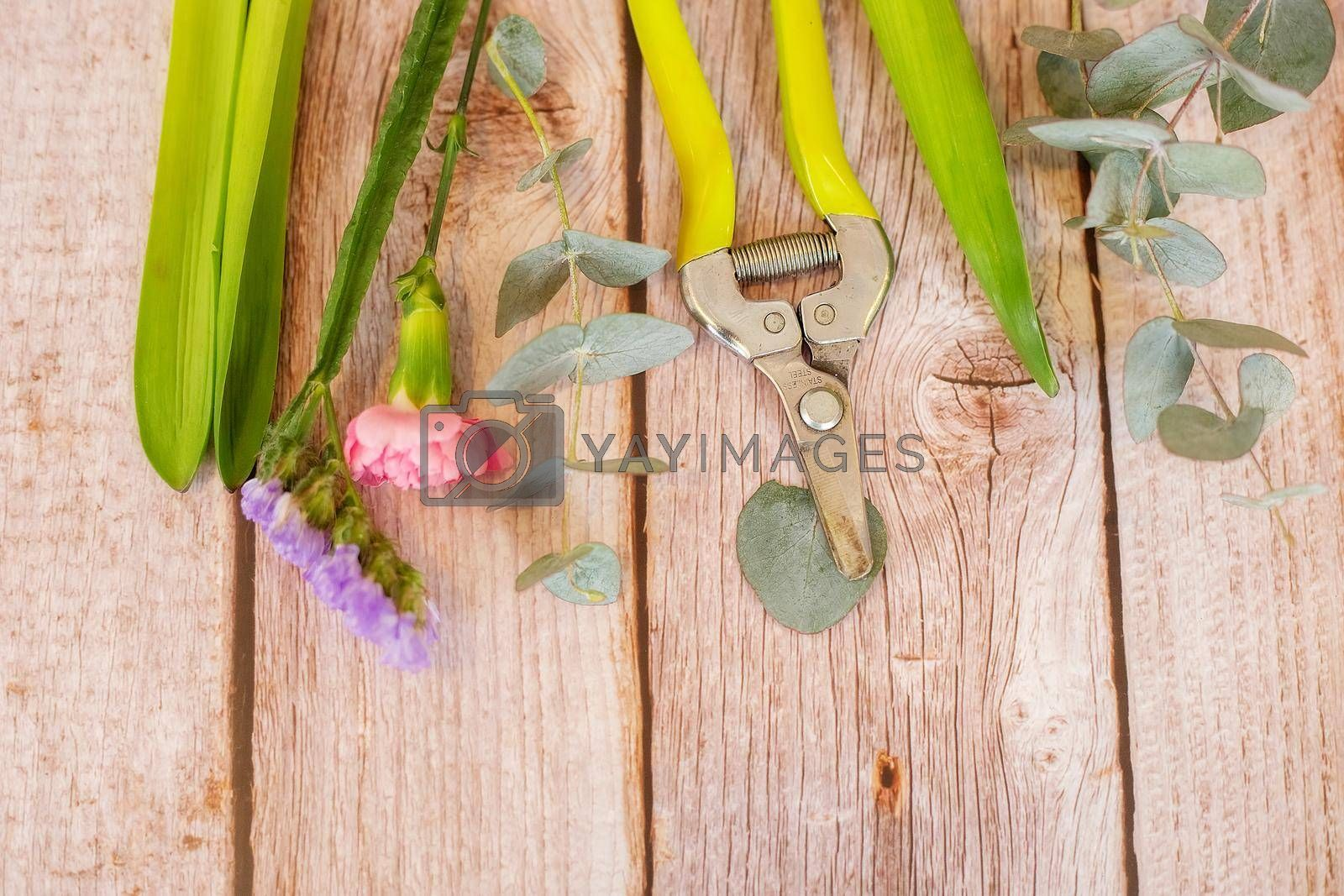 The florist desktop with working tools on light wooden background with place for text.