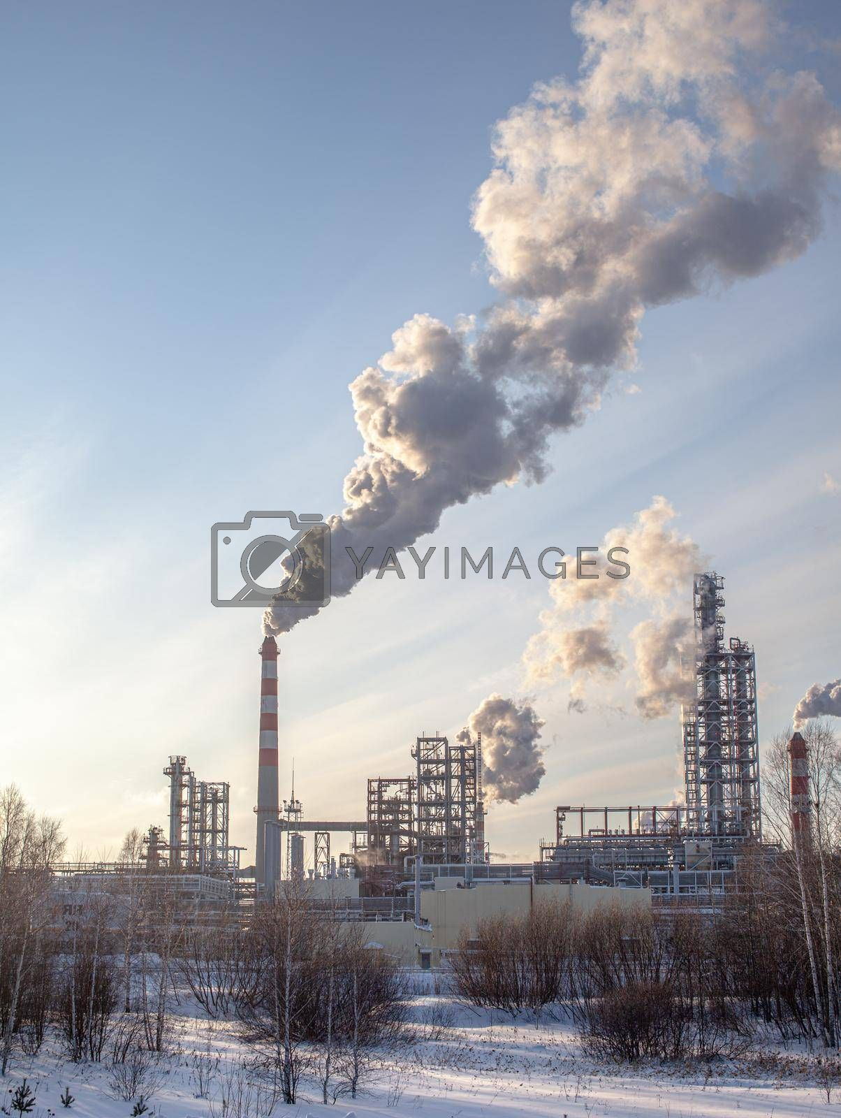 The work of a petrochemical plant. Smoke is coming from the chimney. by AnatoliiFoto