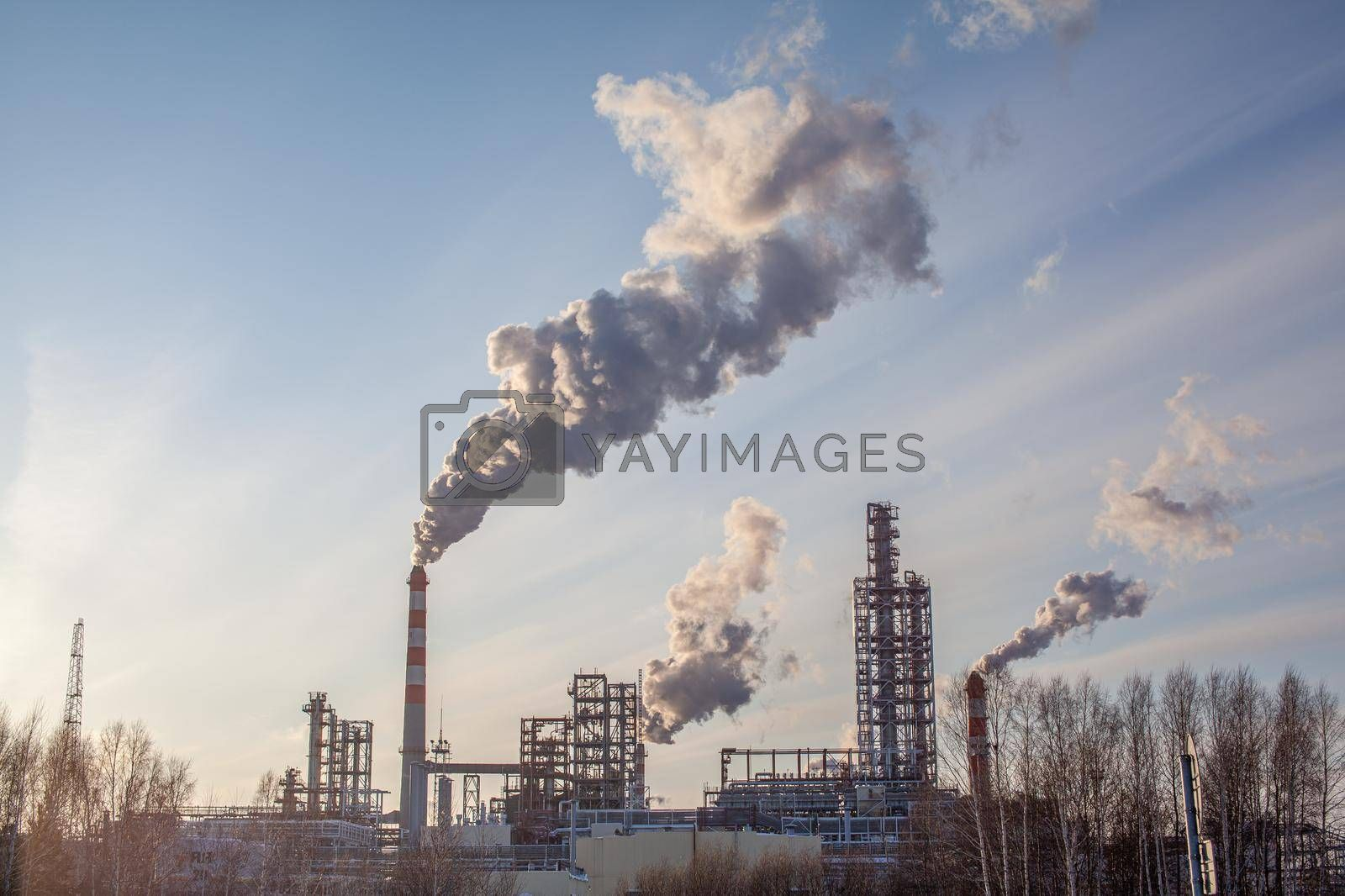 Petrochemical industrial factory of heavy industry, power refinery production with smoke pollution. Thick smoke is coming from the factory's chimney