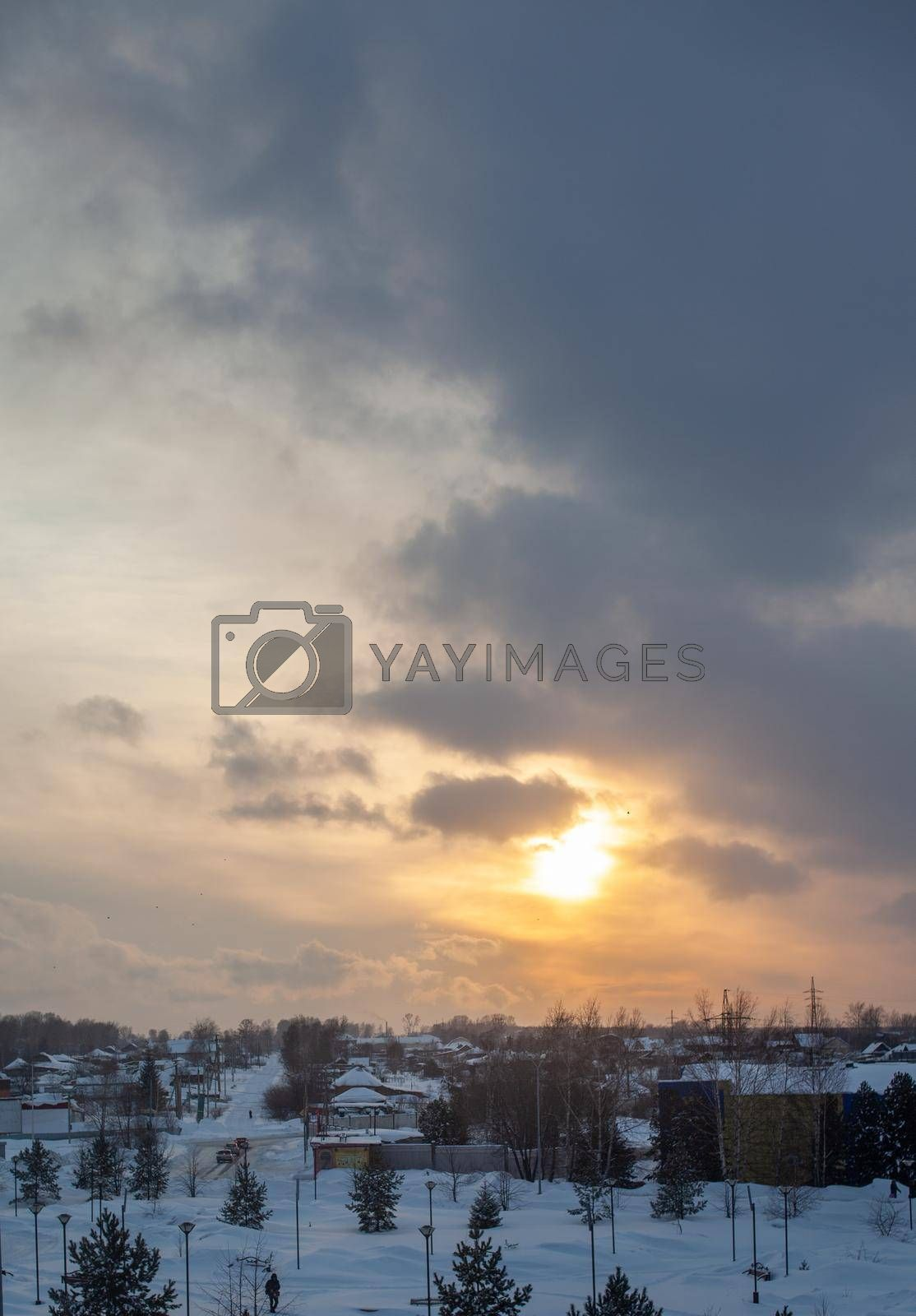 The sun among the clouds over the winter city. Beautiful background. The sky and clouds are painted in different colors.