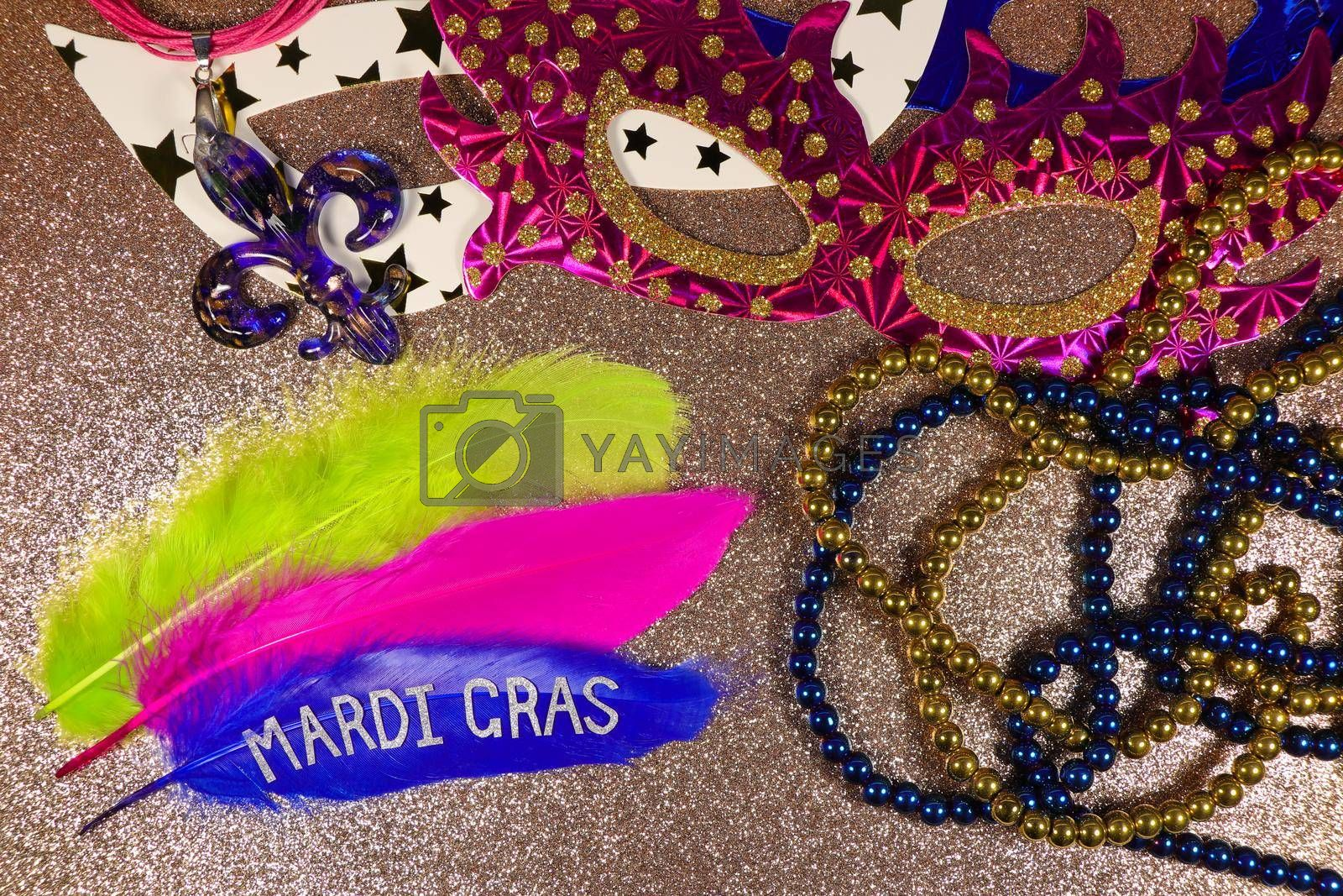 Mardi Gras carnival theme feathers and jewelry with party masks on textured gold surface layout