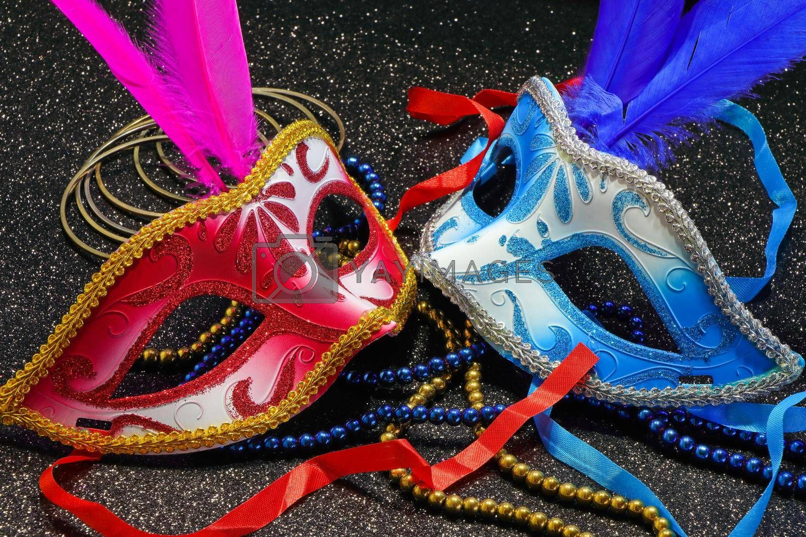 Mardi Gras carnival theme parade face masks with feathers and jewelry on textured black