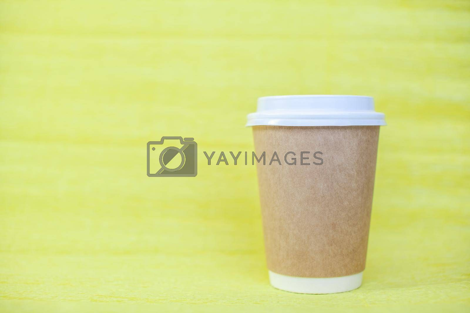 Paper cup of coffee closed with a white lid on a yellow background.  by AnatoliiFoto