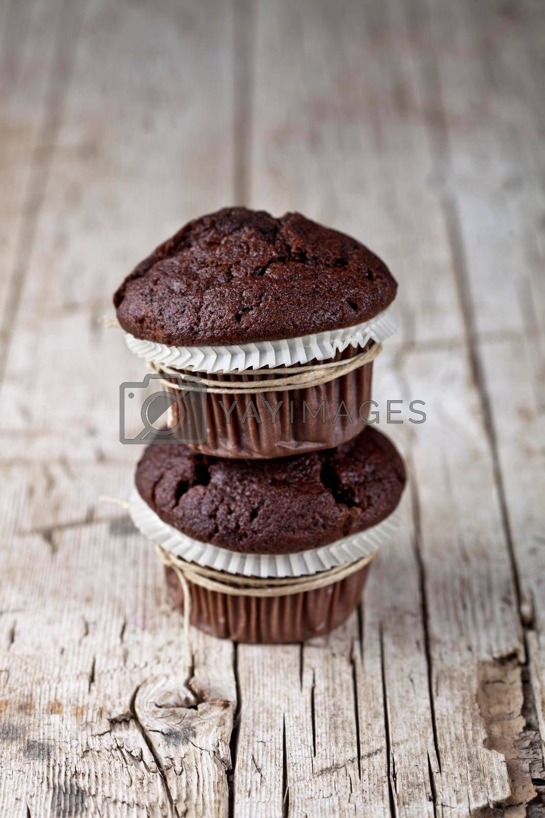 Two dark chocolate dark muffins on rustic wooden table background.