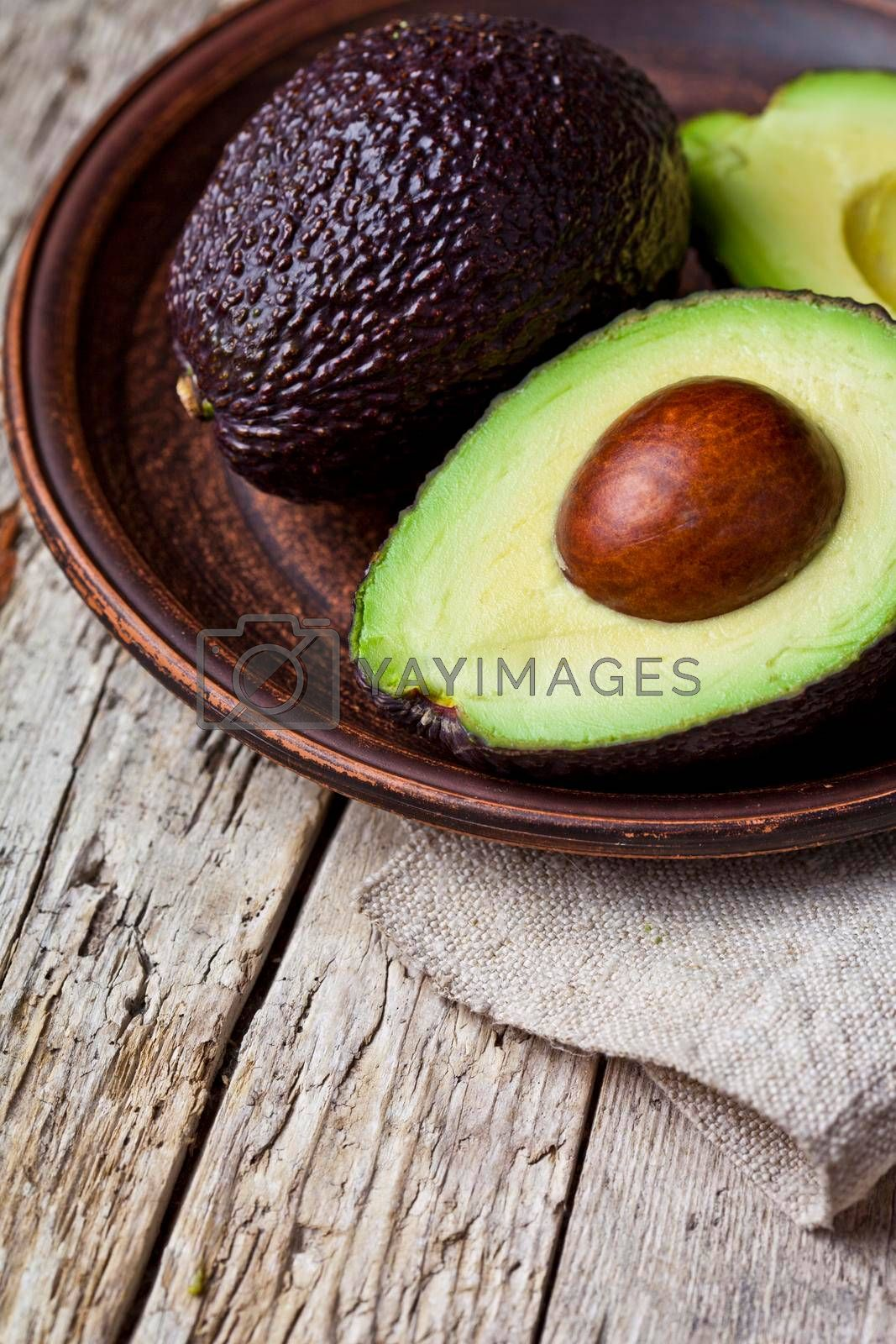 Fresh organic avocado on ceramic plate and linen napkin on rustic wooden table background. Healthy food concept with copy space.