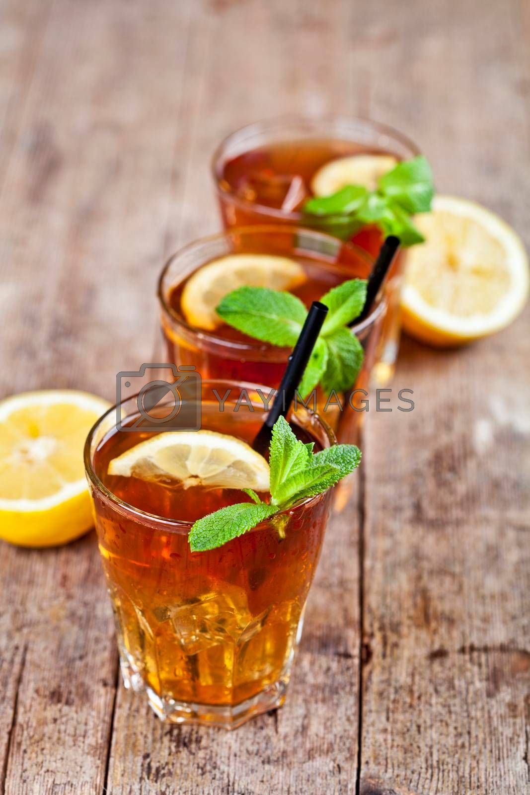Cold iced tea with lemon, mint leaves and ice cubes in three glasses on rustic wooden table background.