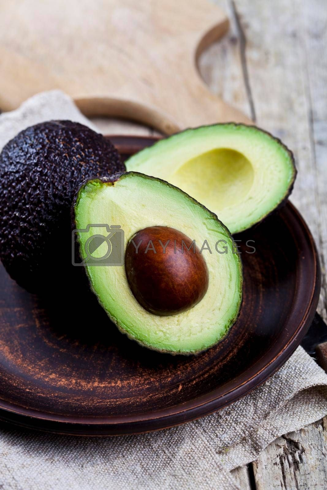 Fresh organic avocado on ceramic plate and linen napkin on rustic wooden table background. Healthy food concept.
