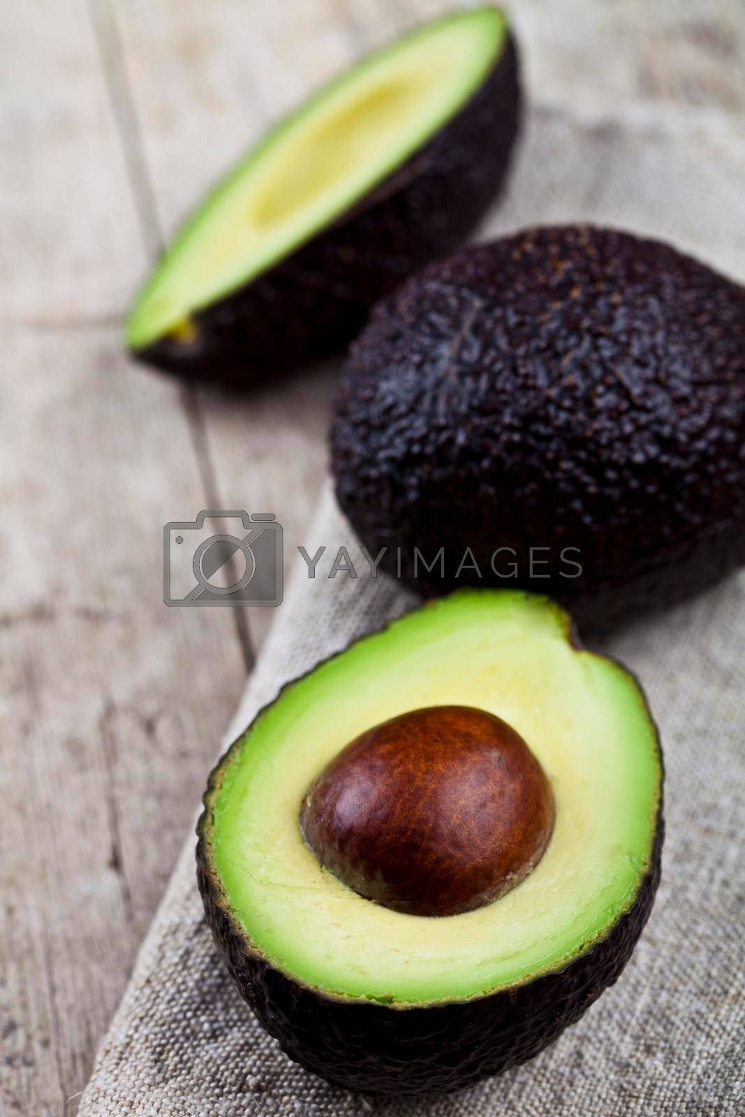 Organic avocado on linen napkin on rustic wooden table background. Fresh avocado halves on rustic wooden backround with copy space. Healthy food concept.