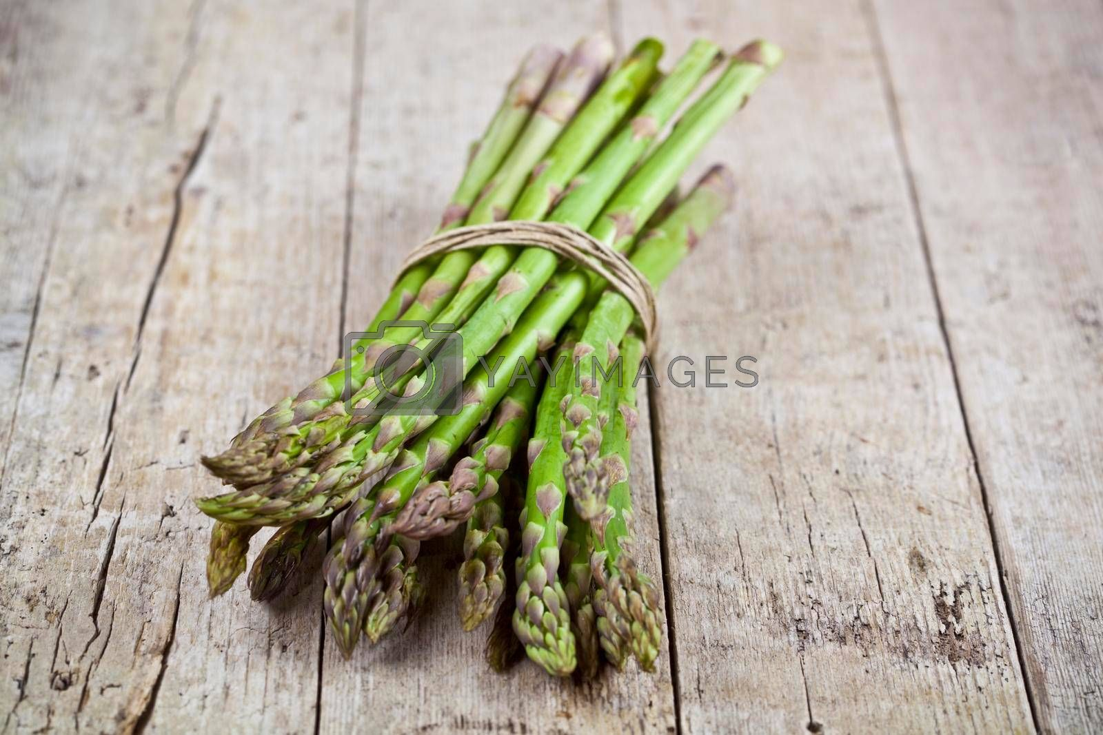 Bunch of fresh raw garden asparagus on rustic wooden table background. Green spring vegetables. Edible sprouts of asparagus.