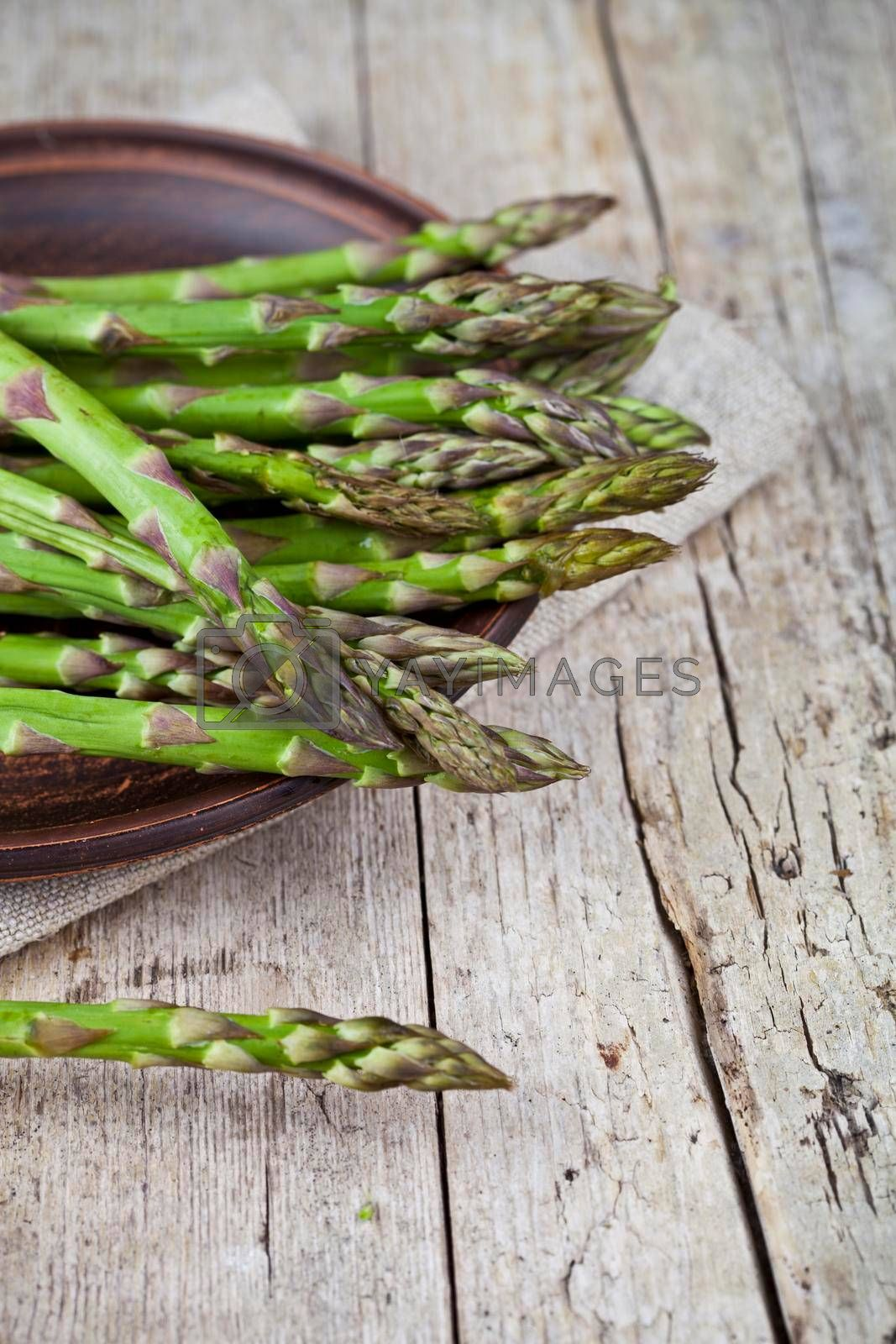 Fresh raw garden asparagus closeup on brown ceramic plate and linen napkin on rustic wooden table background. Green spring vegetables. Edible sprouts of asparagus. With copy space.