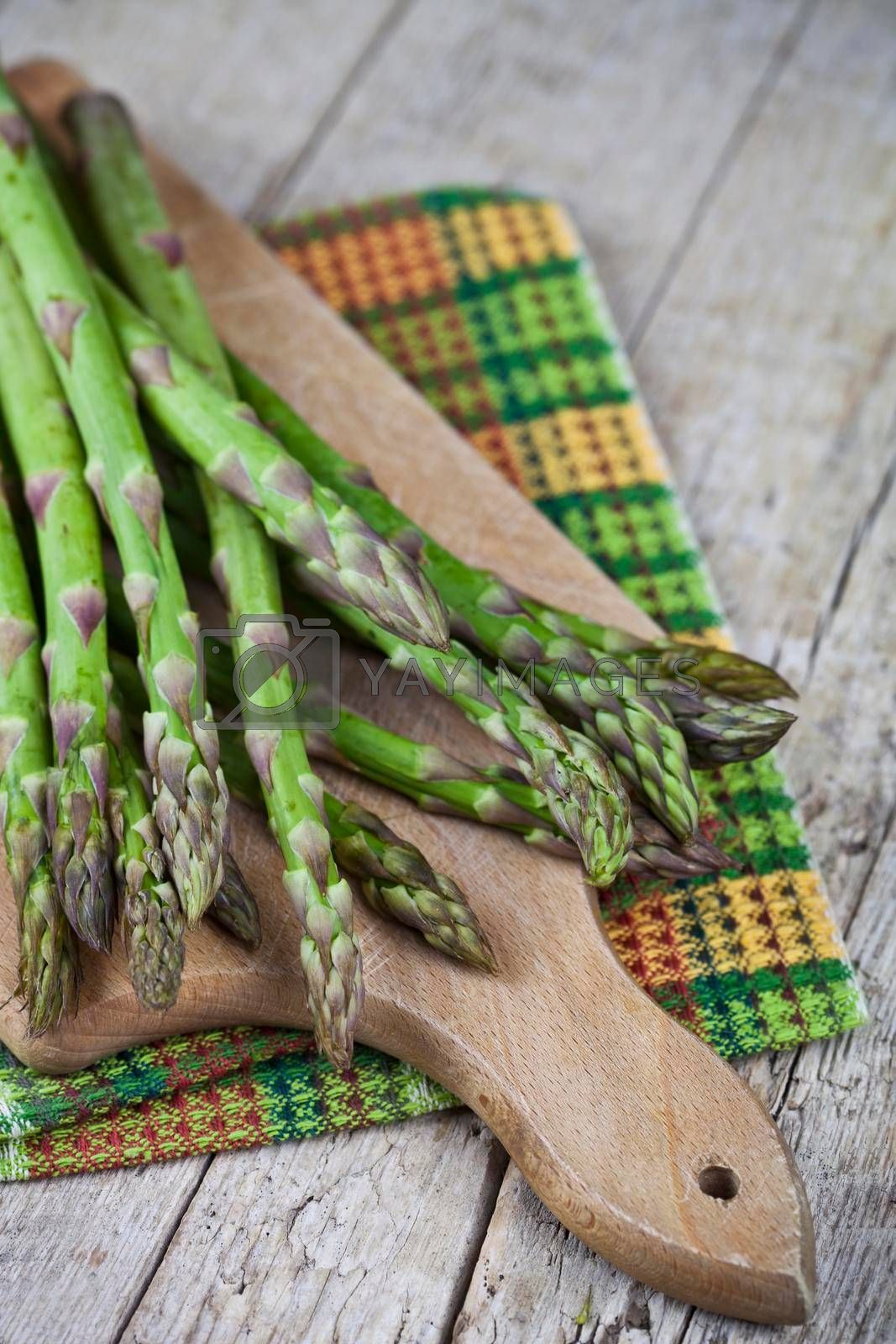 Organic raw garden asparagus on cutting board on rustic wooden table background. Green spring vegetables and cotton napkin. Edible sprouts of asparagus.