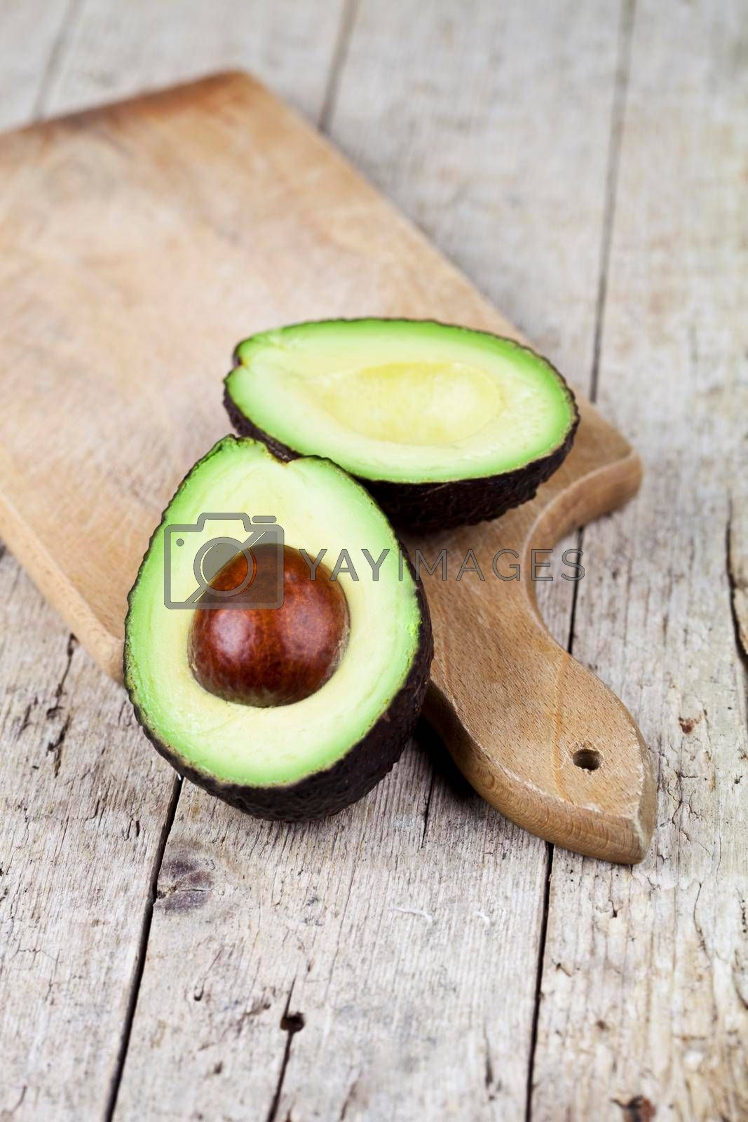 Fresh organic avocado halves on cutting board on old wooden table background. Healthy food concept.