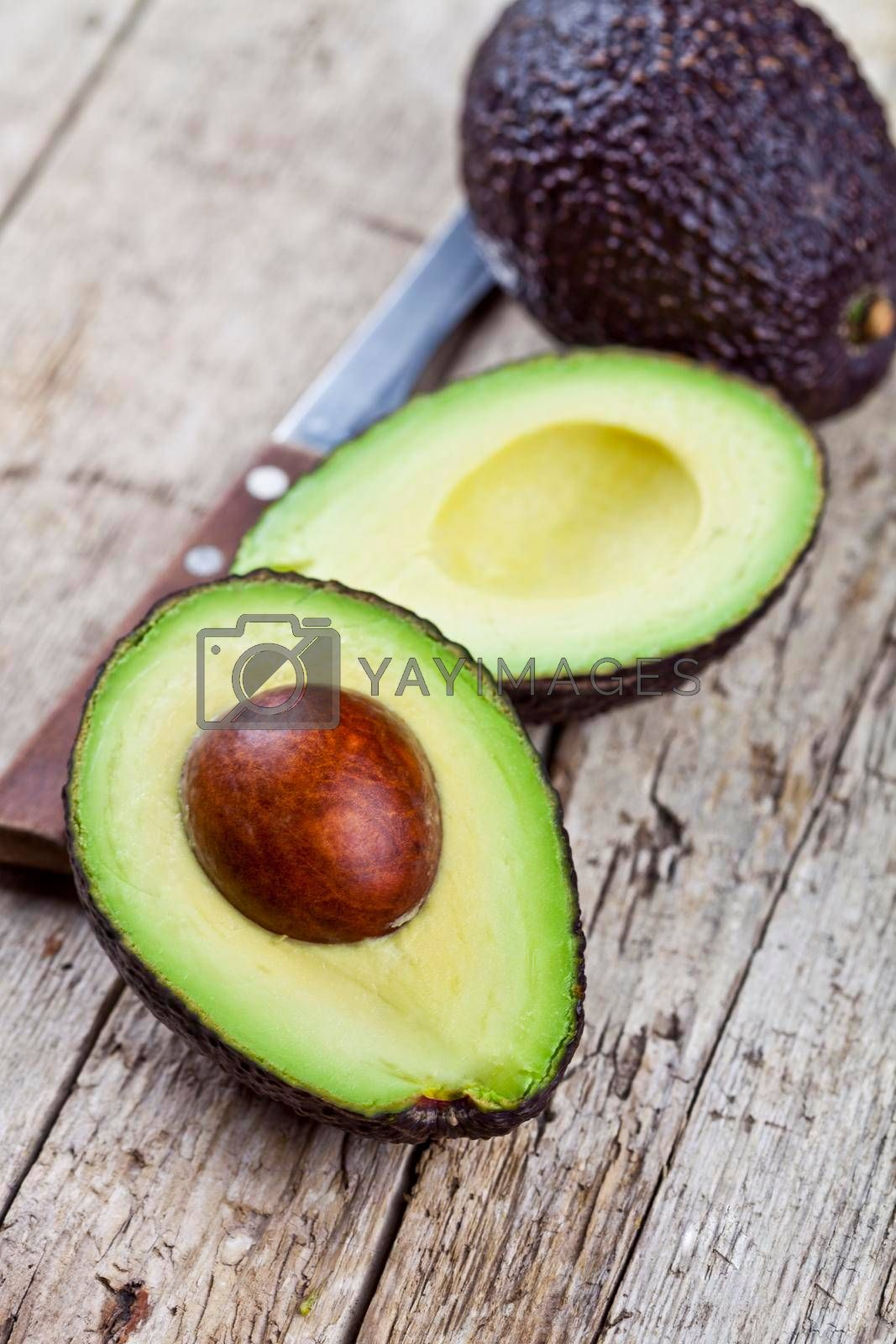 Fresh organic avocado and knife on old wooden table background. Fresh avocado halves on rustic wooden backround. Healthy food concept.