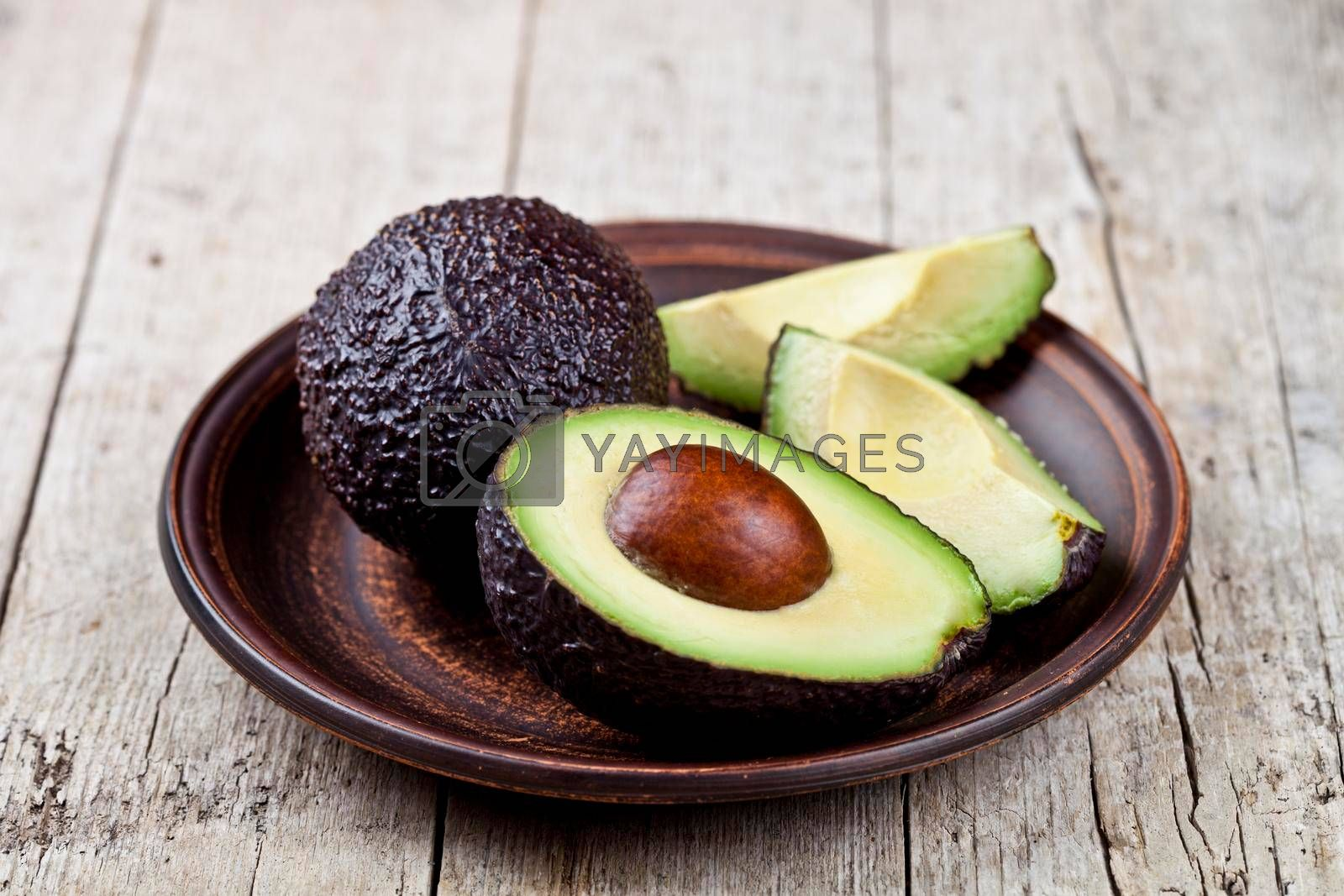 Fresh organic avocado on ceramic plate on rustic wooden table background. Healthy food concept.