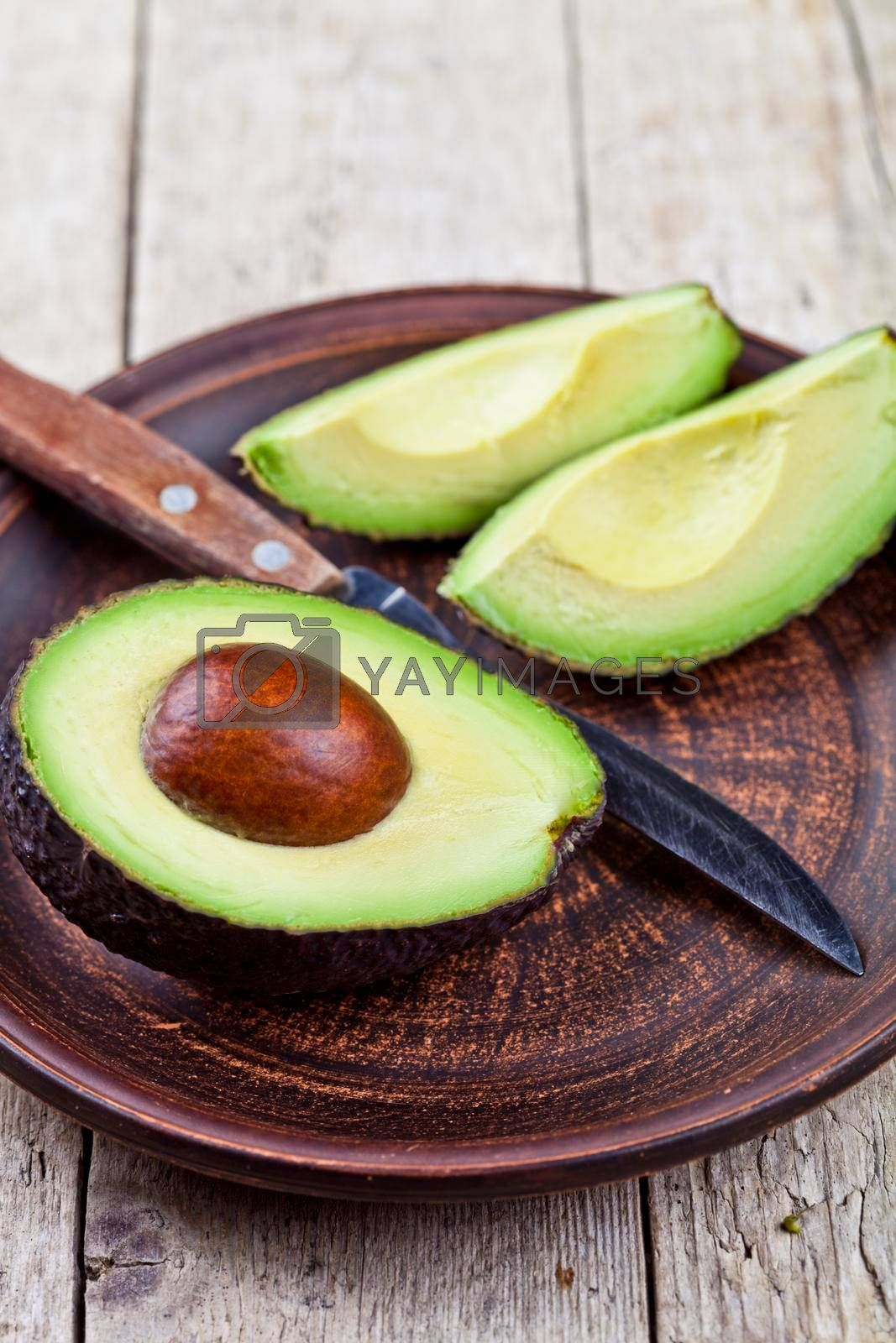 Fresh organic avocado on ceramic plate and knife on rustic wooden table background. Healthy food concept.