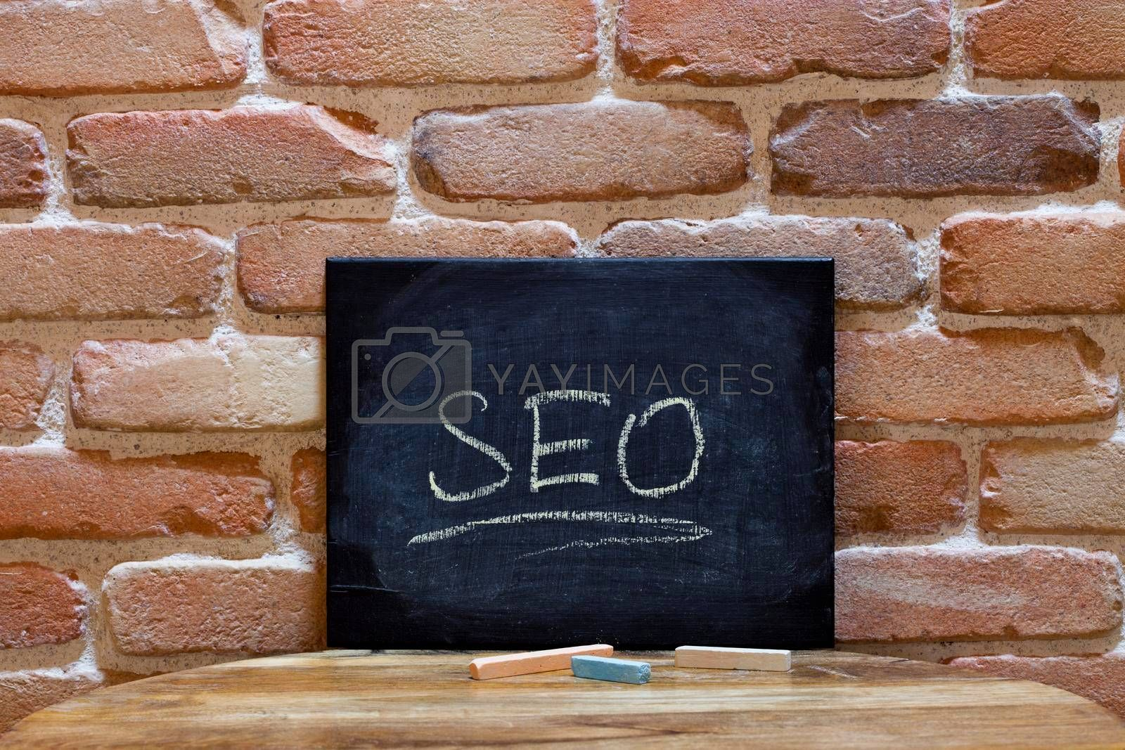 Black board with the word SEO drown by hand on wooden table on brick wall background. For business presentation.