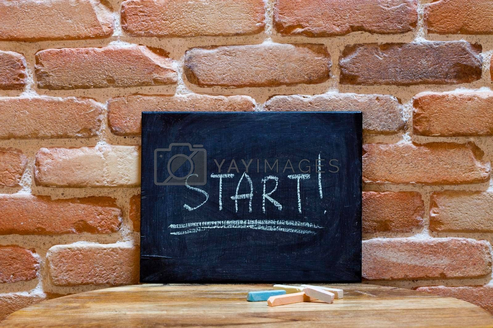 """Black board with the word """"Start!"""" drown by hand on wooden table on brick wall background. For business presentation."""