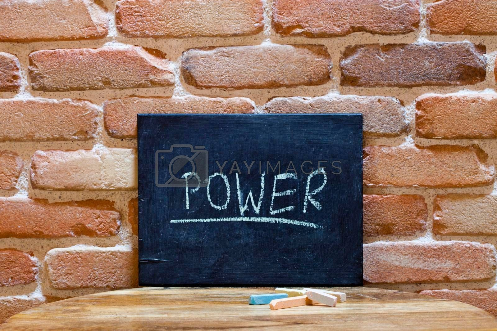 """Chalk board with the word """"Power"""" drown by hand on wooden table on brick wall background. For business presentation."""
