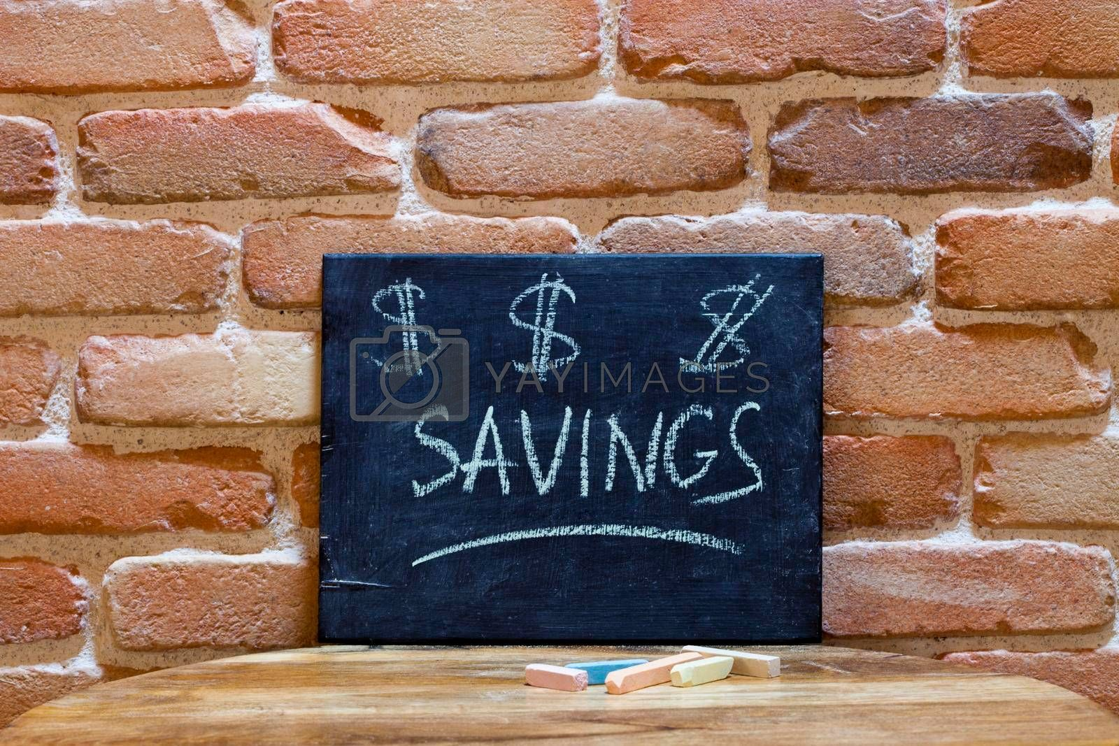 """Black board with the word """"Savings"""" drown by hand on wooden table on brick wall background. For business presentation."""