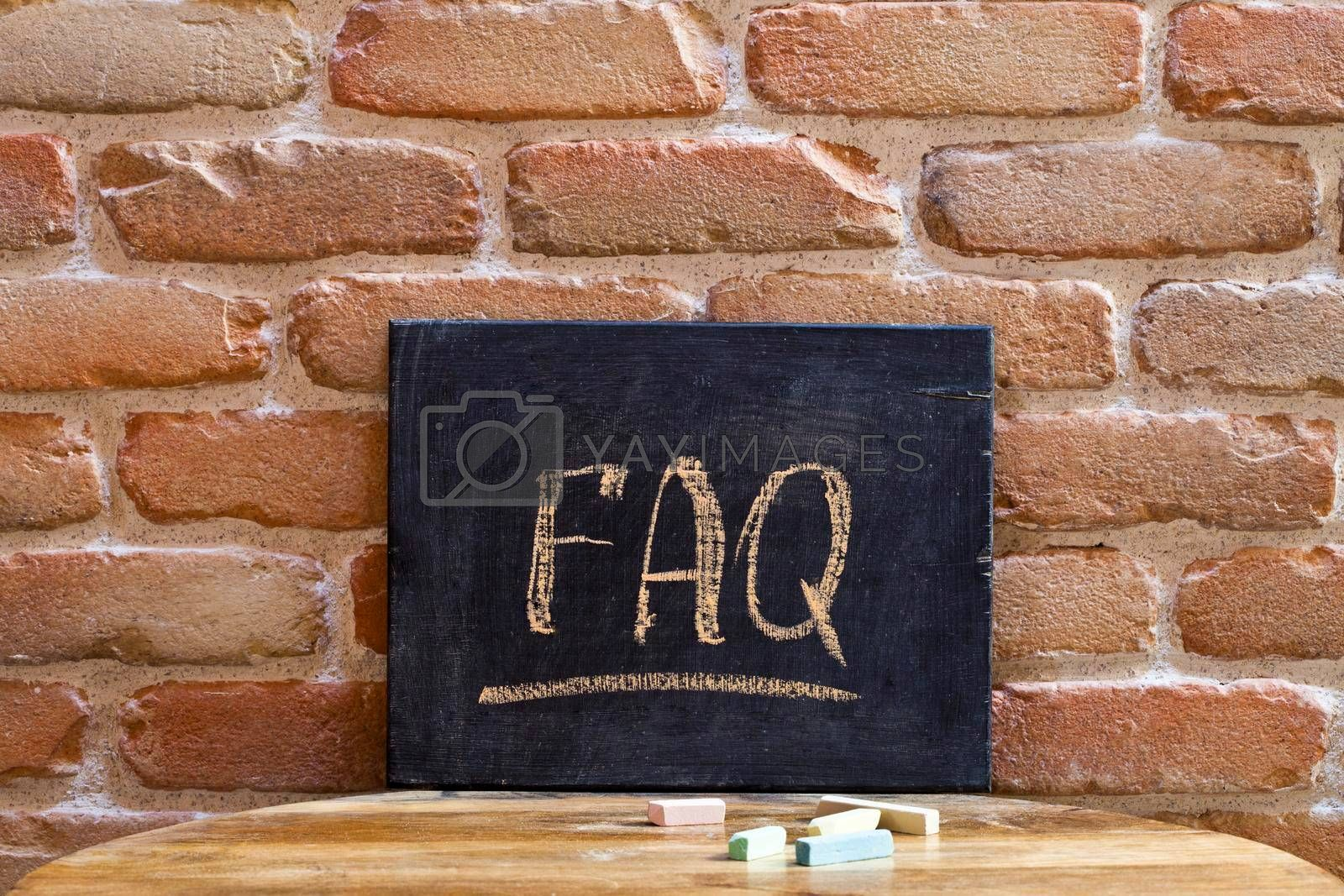 Black board with the word FAQ drown by hand on wooden table on brick wall background. For business presentation.