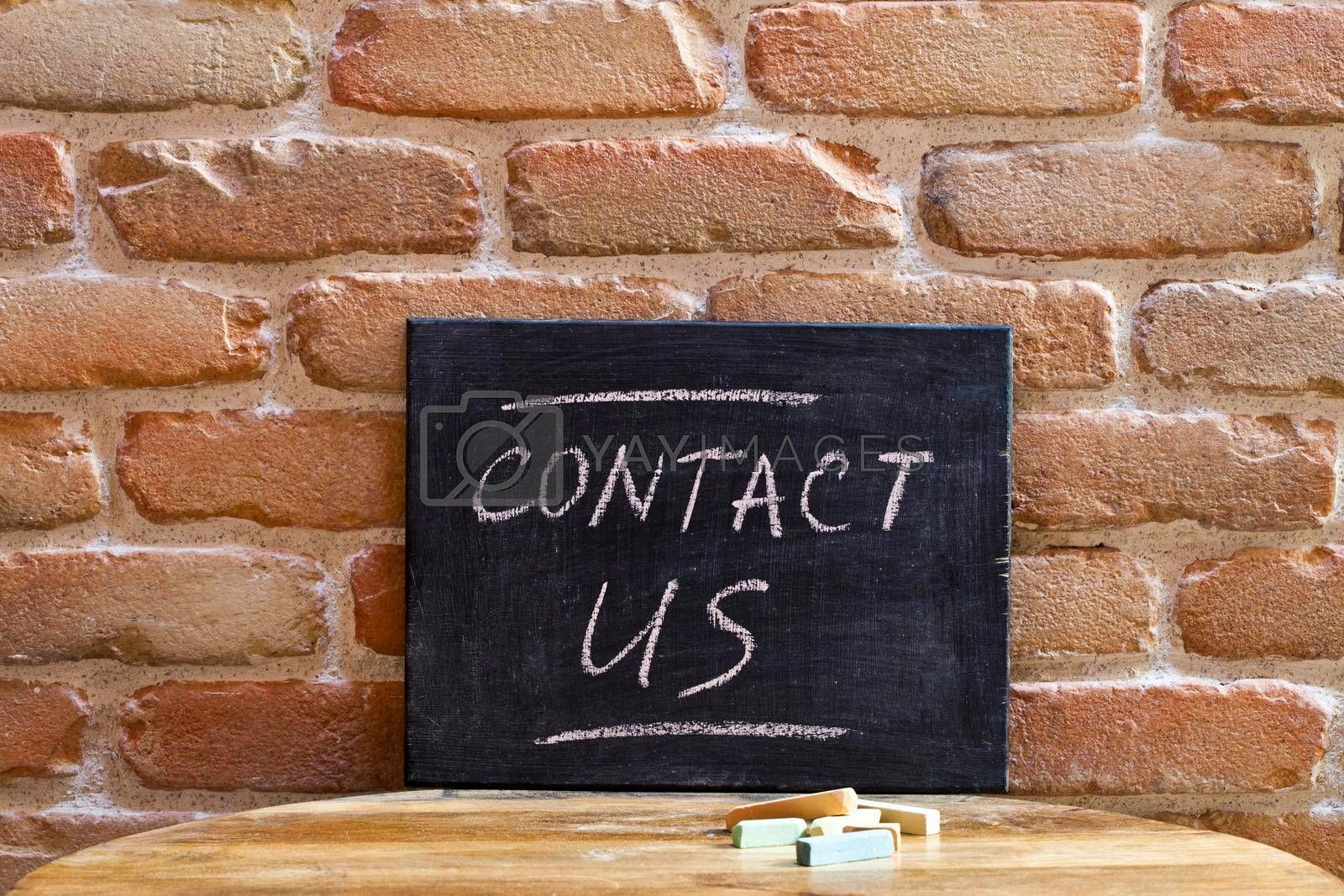 Black board with the phrase CONTACT US drown by hand on wooden table on brick wall background. For business presentation.