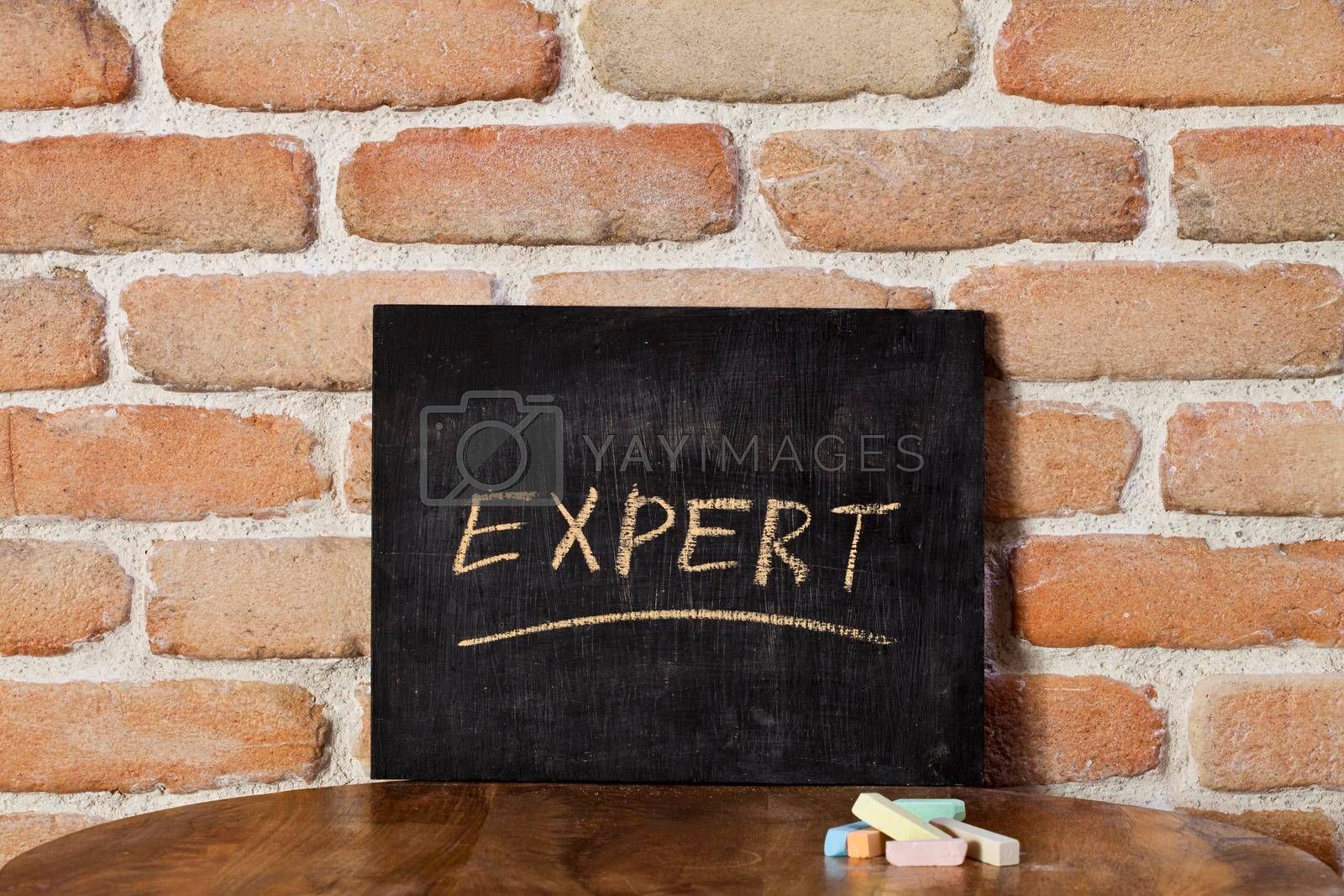 Chalk board with the word EXPERT drown by hand on wooden table on brick wall background. For business presentation.