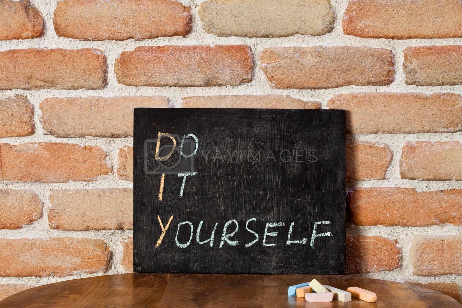 Black chalkboard with the phrase DO IT YOURSELF drown by hand on wooden table on brick wall background. Presentation concept.