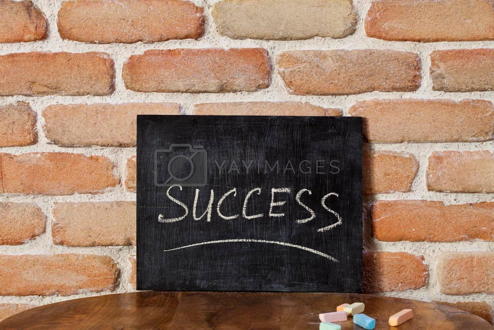 Chalk board with the word SUCCESS drown by hand on wooden table on brick wall background. For business presentation.