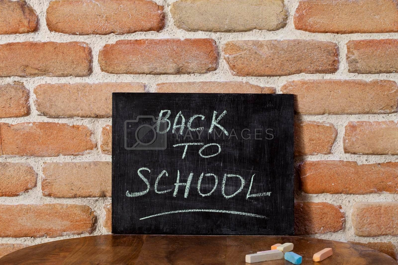 Black chalkboard with the phrase BACK TO SCHOOL drown by hand on wooden table on brick wall background. Presentation concept.