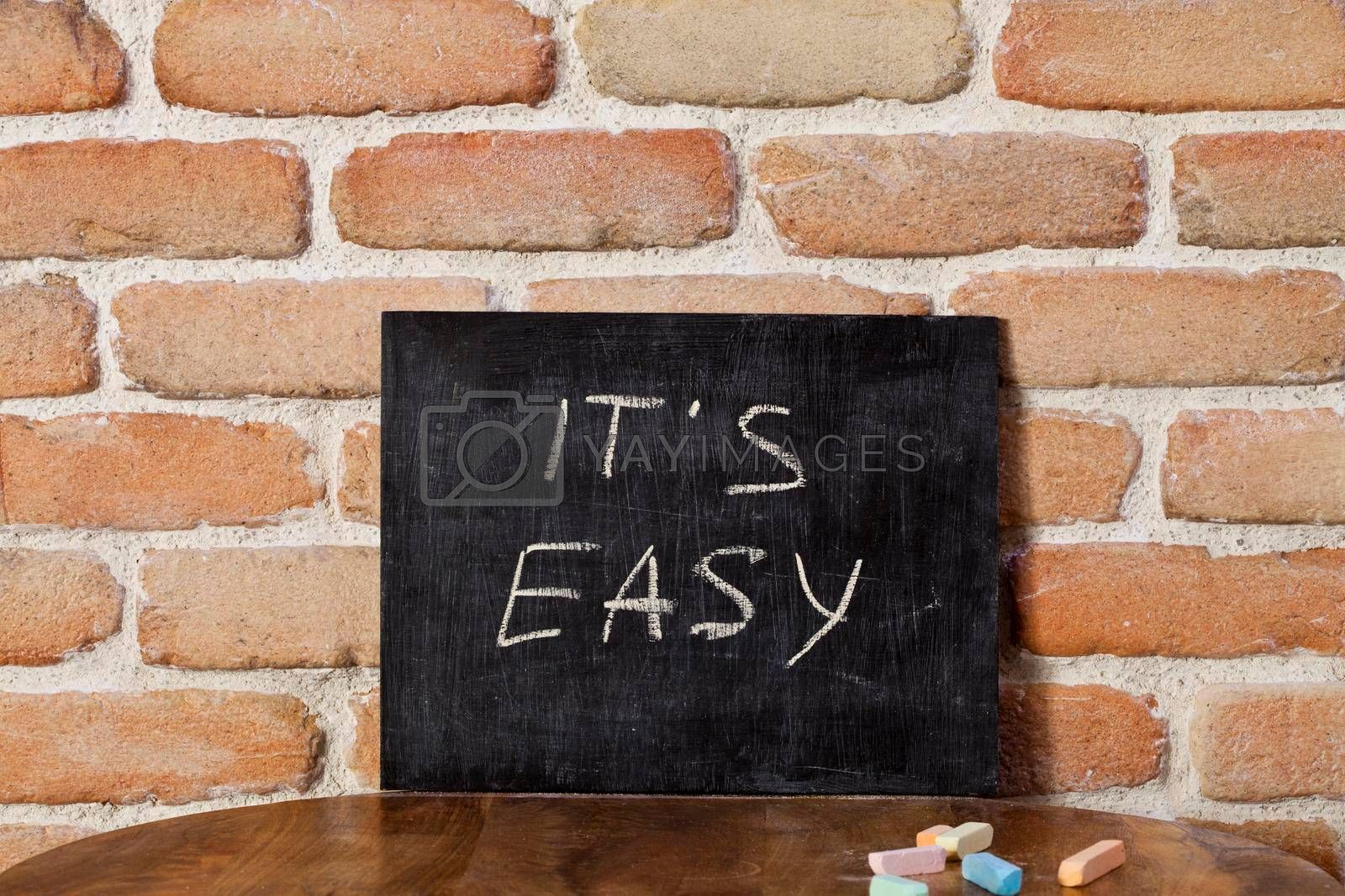 Black board with the phrase IT'S EASY drown by hand on wooden table on brick wall background. Presentation concept.