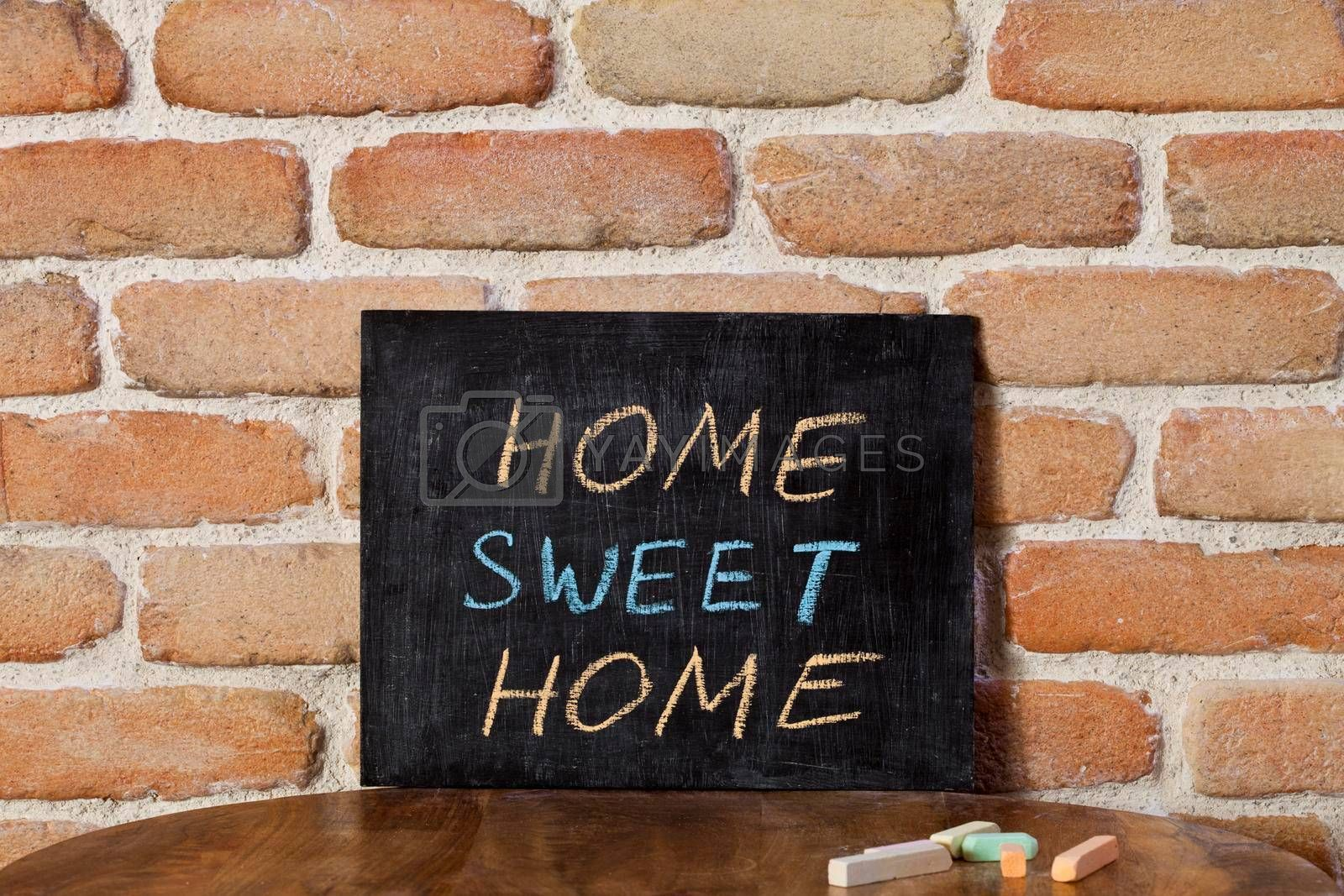 Black chalkboard with the phrase HOME SWEET HOME drown by hand on wooden table on brick wall background. Presentation concept.