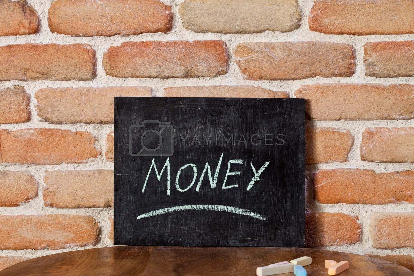 Chalk board with the word MONEY drown by hand on wooden table on brick wall background. For business presentation.