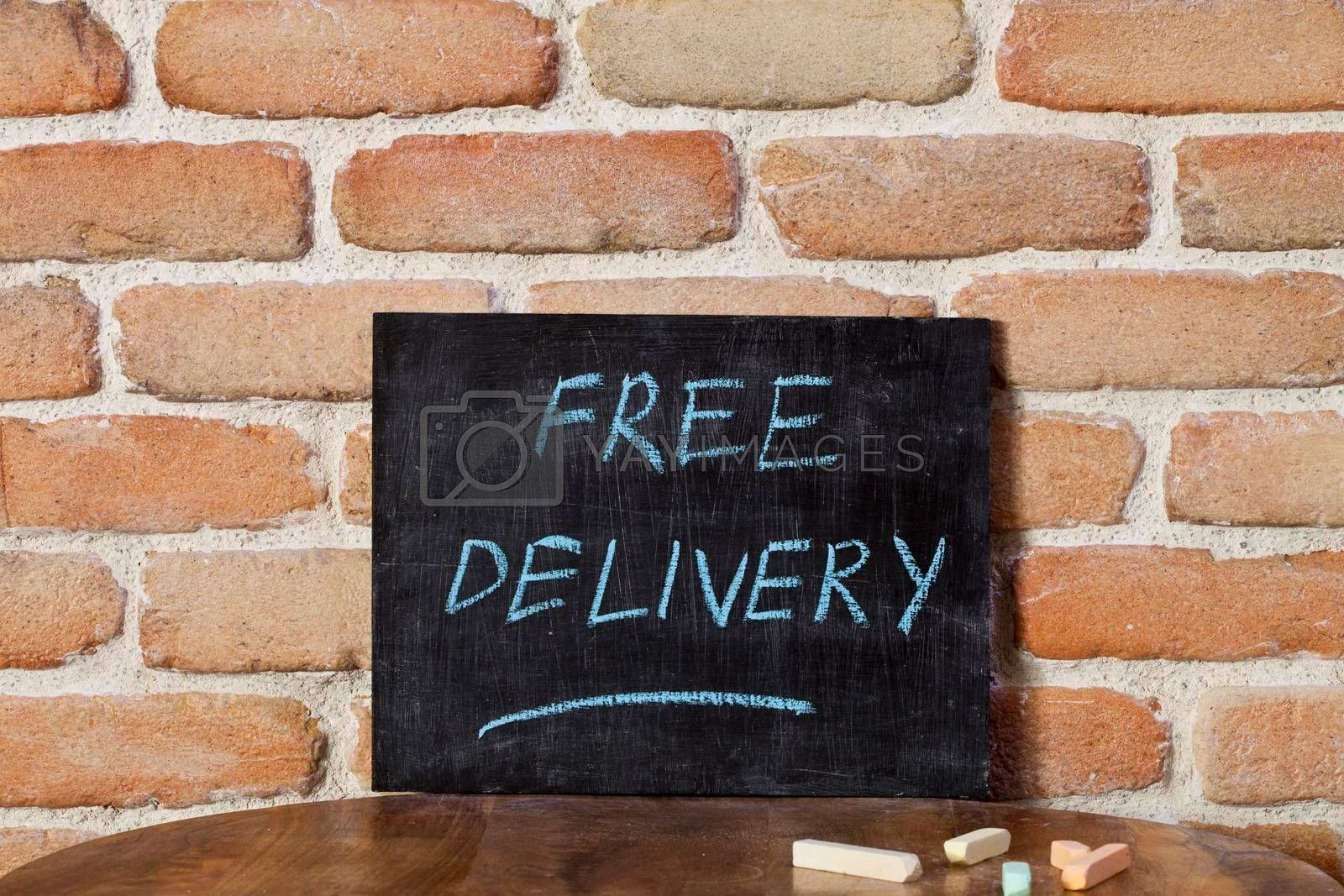 Black chalkboard with the phrase FREE DELIVERY drown by hand on wooden table on brick wall background. For business presentation.