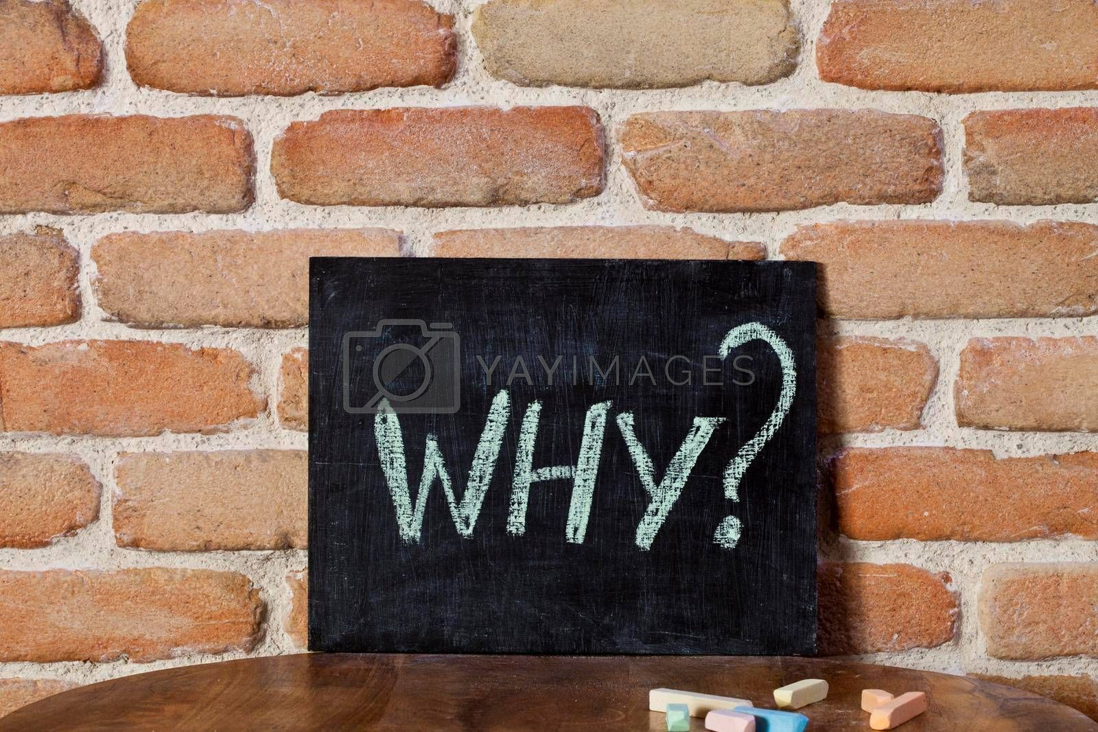 Black board with the word WHY? drown by hand on wooden table on brick wall background. For business presentation.