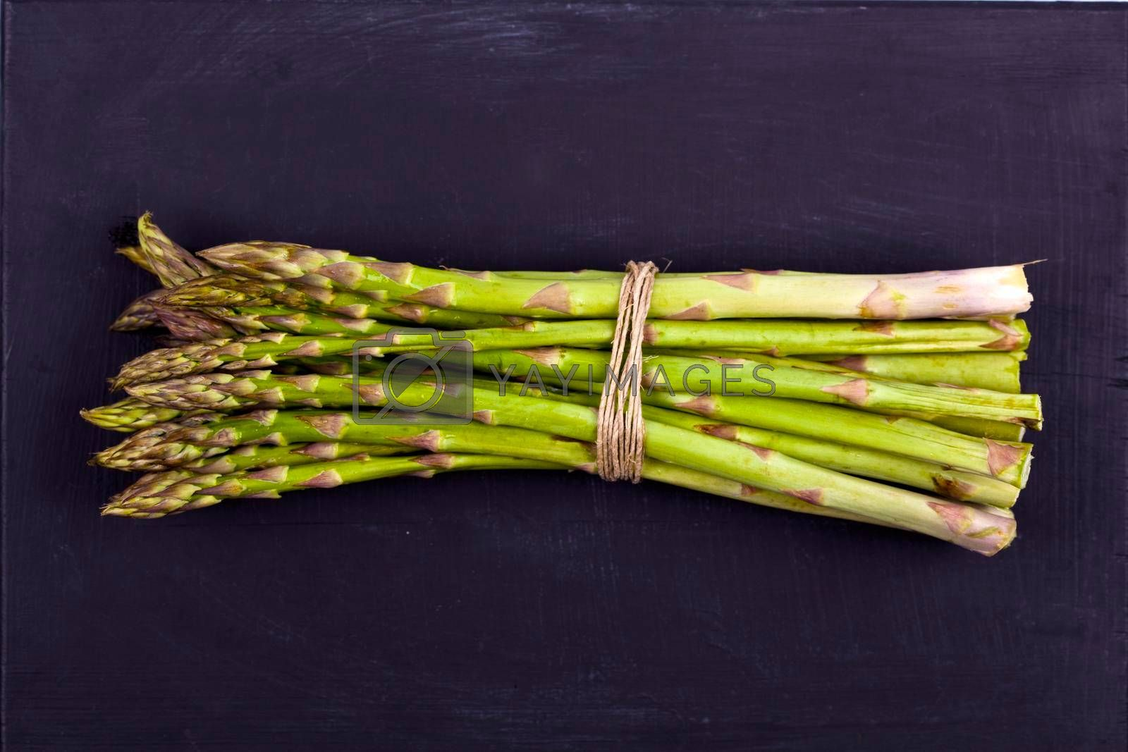 Bunch of fresh raw garden asparagus on black board background. Green spring vegetables.Top view of edible sprouts of asparagus.