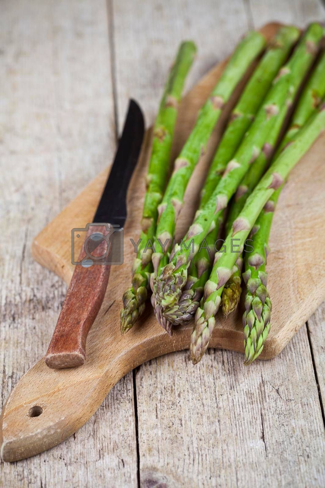 Fresh raw garden asparagus and knife closeup on cutting board on rustic wooden table background. Green spring vegetables. Edible sprouts of asparagus.