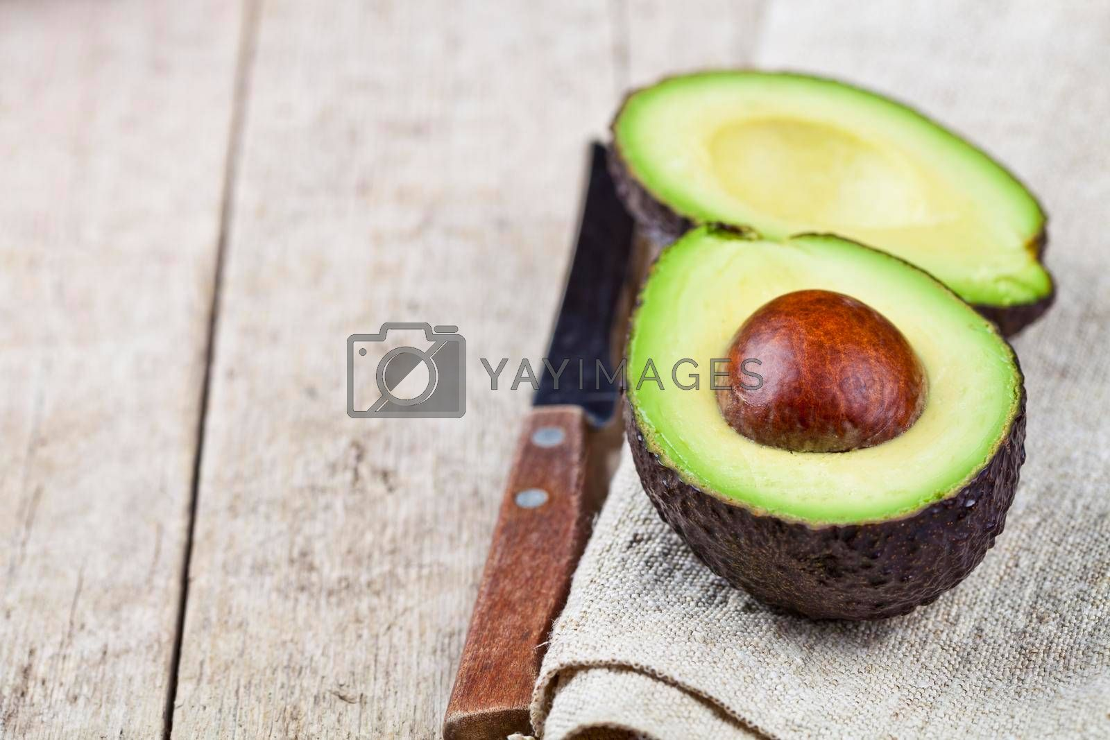 Avocado and knife on linen napkin old wooden table background. Fresh avocado halves on rustic wooden backround with copy space. Healthy food concept.