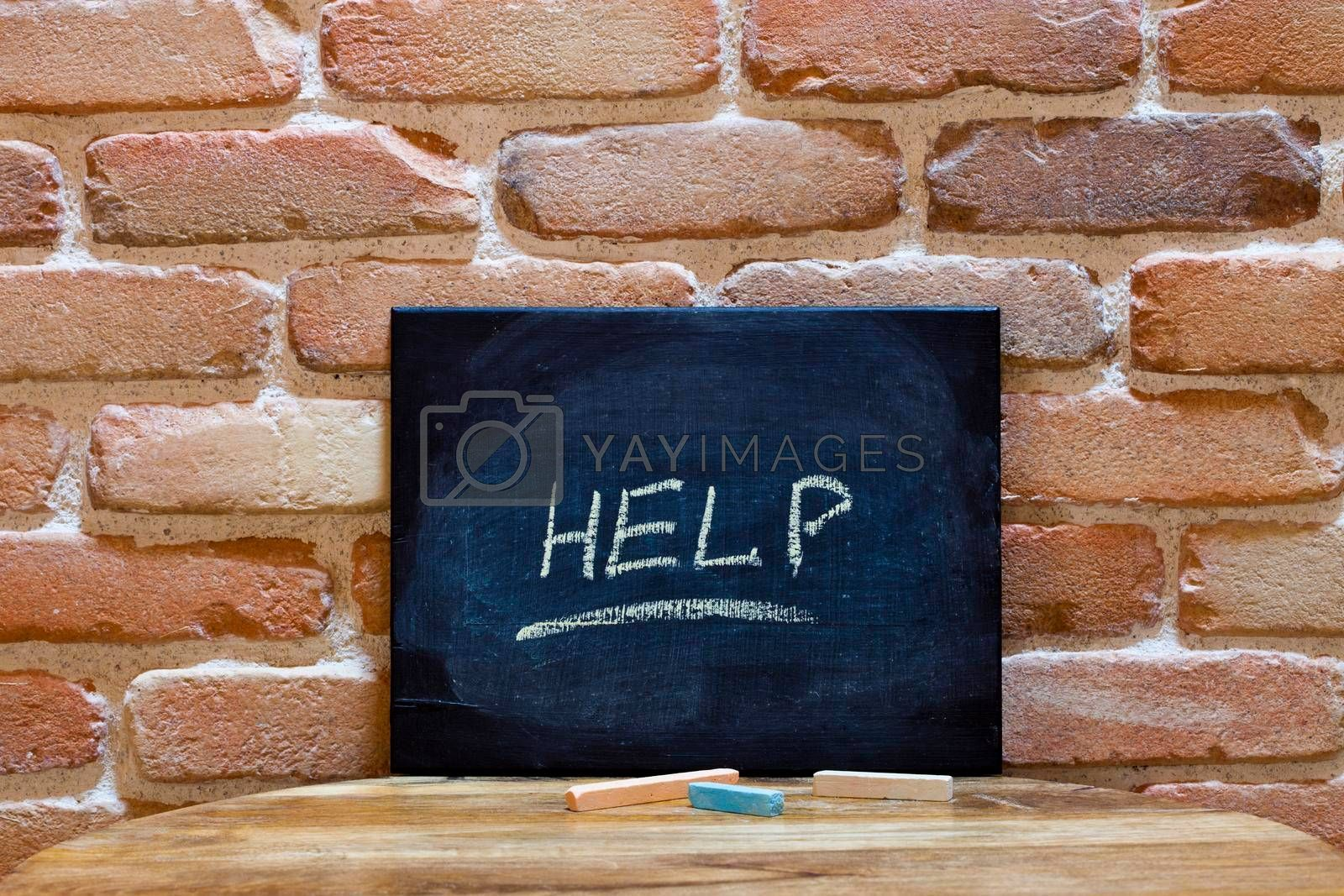 """Blackboard with the word """"Help"""" drown by hand on wooden table on brick wall background. For business presentation."""