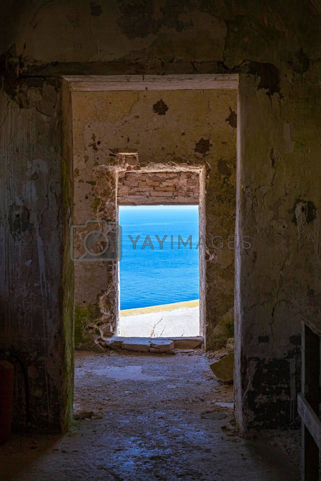 View through old abandoned dilapidated building on the blue seascape. Adriatic Sea. Puglia, Italy.
