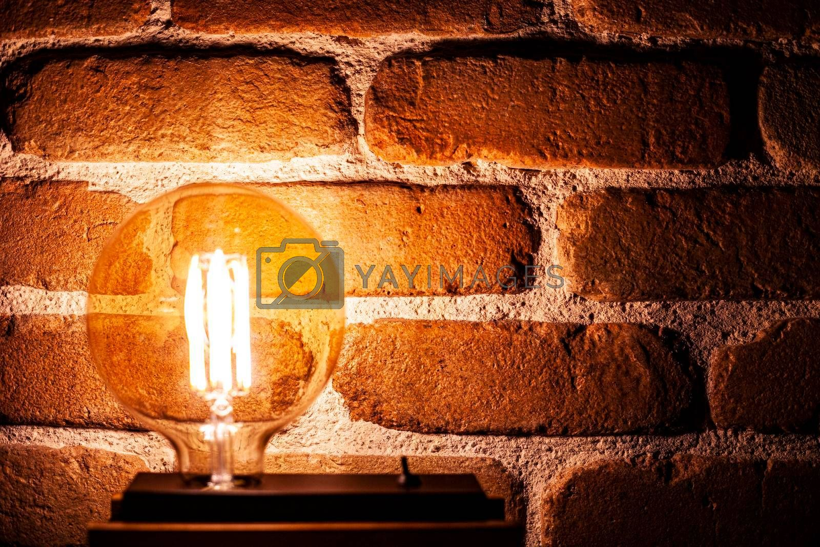 Illuminated grunge red brick wall background with copy space.