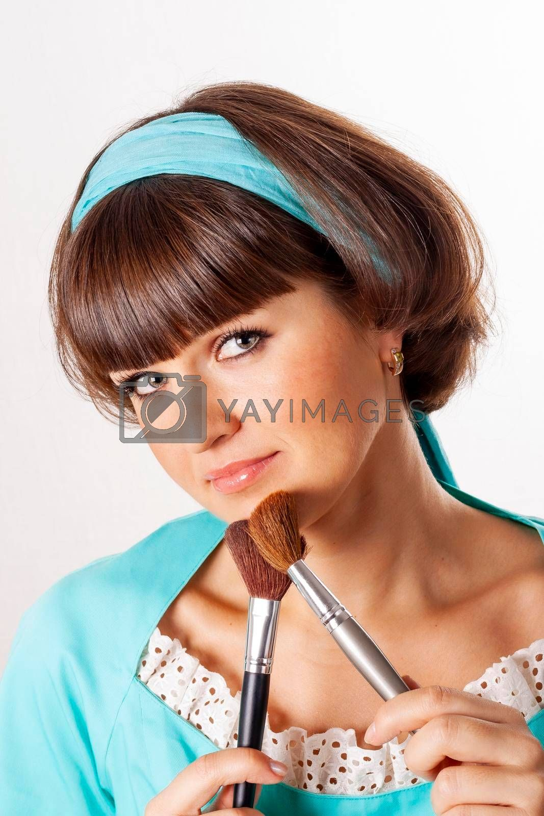 Portrait of attractive brunet woman in blue dress with two make-up brushes isolated on white background.