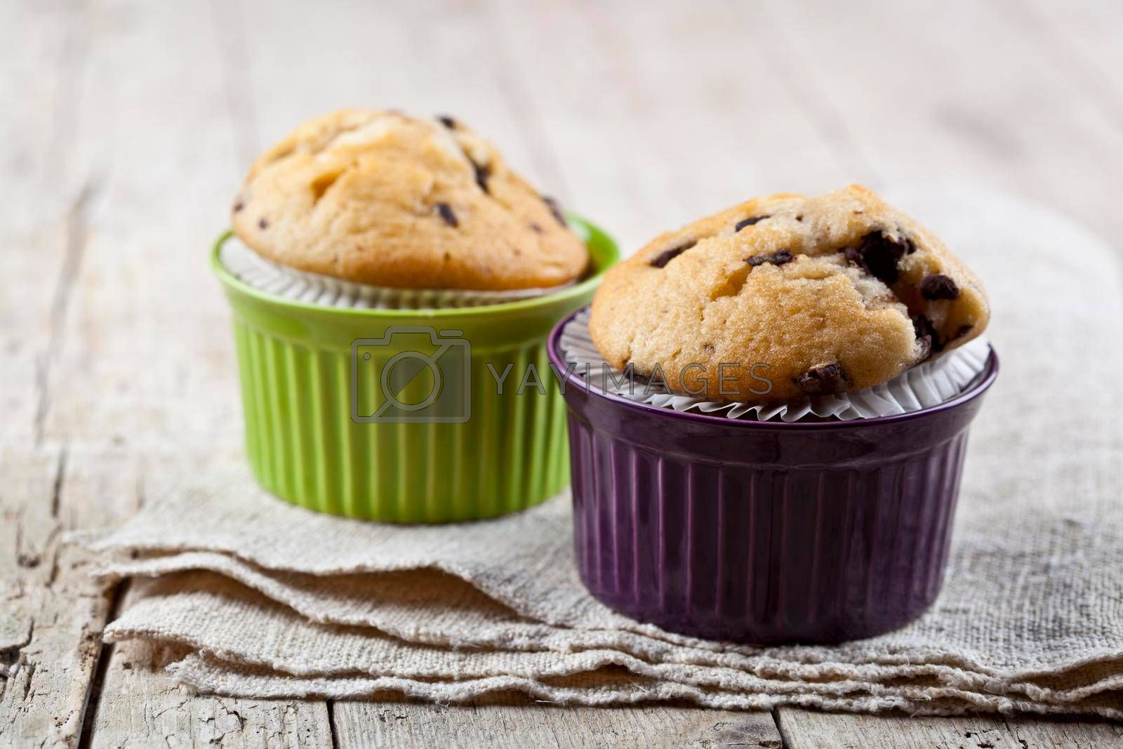 Homemade fresh muffins on ceramic bowls on linen napkin on rustic wooden table background.