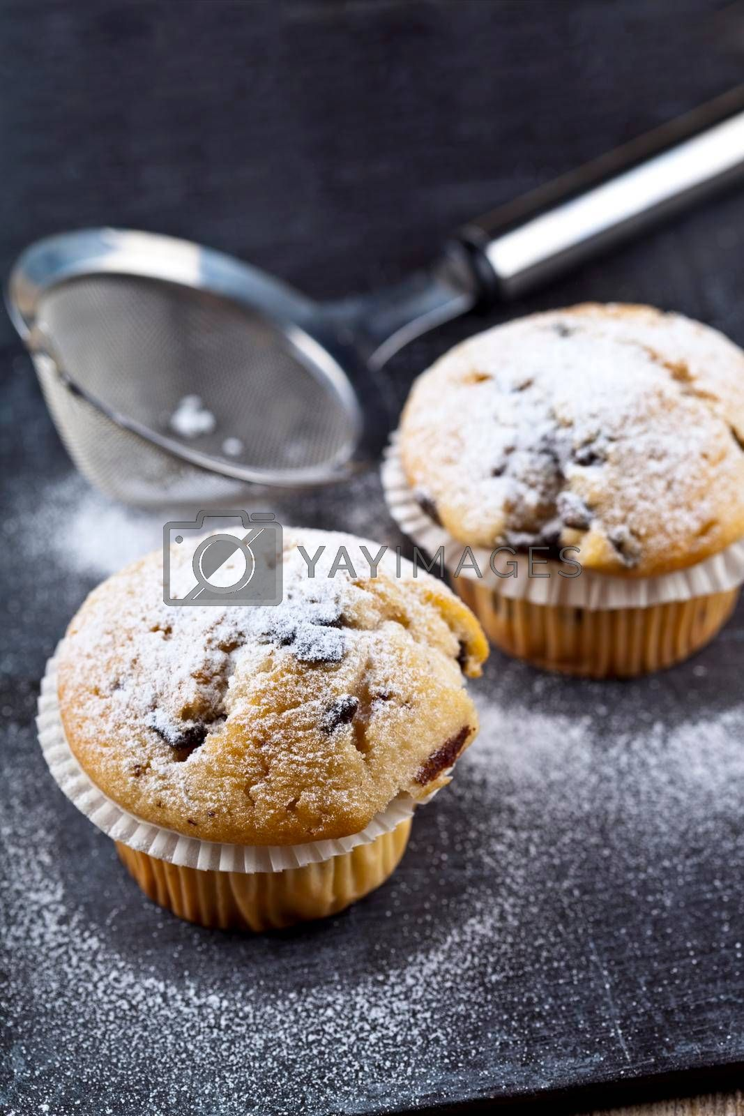 Two fresh homemade muffins with sugar powder and metal strainer closeup on black board background.