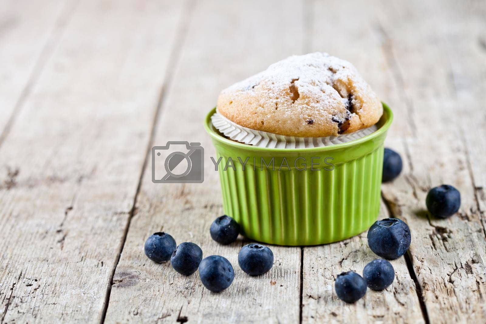 Homemade fresh muffin on ceramic green bowl with blueberries on rustic wooden table background.