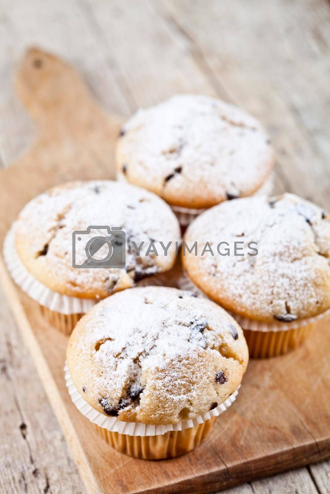 Homemade fresh muffins with sugar powder on cutting board rustic wooden table background.