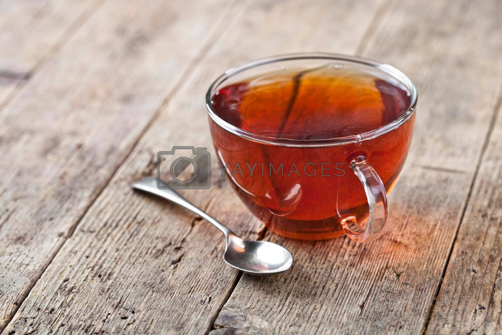 Cup of fresh tea and vintage spoon on rustic wooden table background. Transparent tea cup.